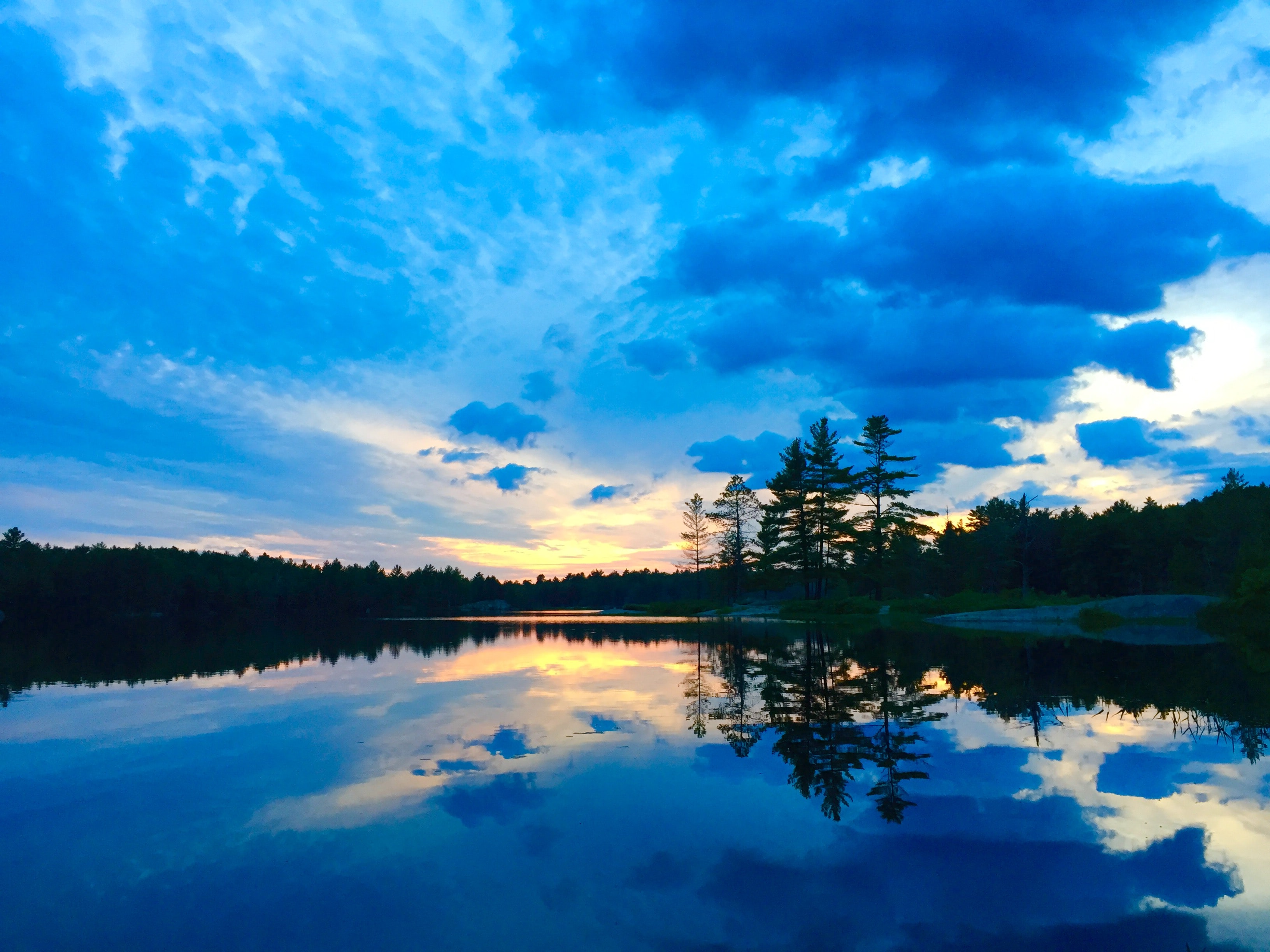 A bright blue cloudy sky and its reflection in a lake at Kawartha Highlands Provincial Park