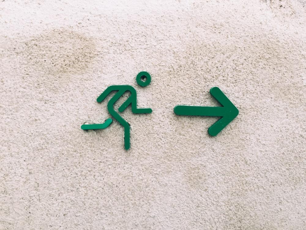 A green sign of a stick figure guy running towards a green arrow.