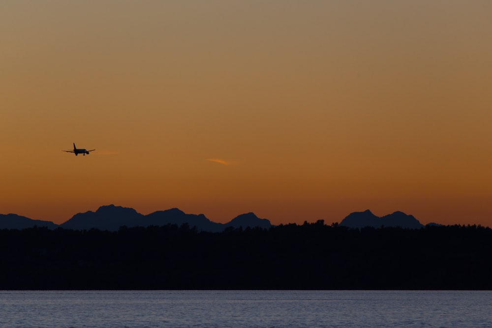 silhouette photo of airplane during sunset