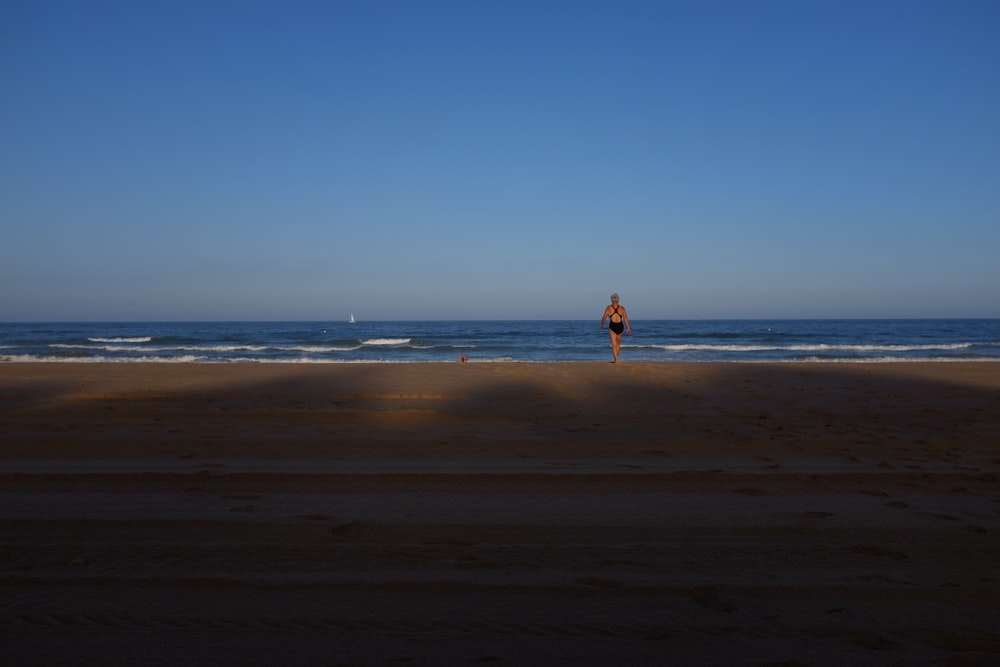 woman in black one-piece swimsuit facing blue wavy ocean under clear blue sky