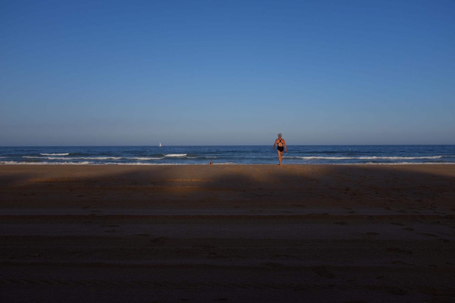 Woman in swimsuit walking on the sandy beach towards the ocean