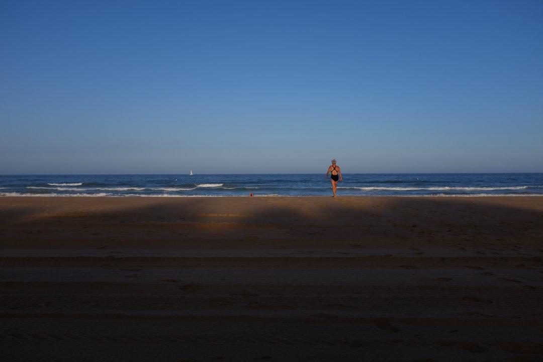 Woman walking towards ocean