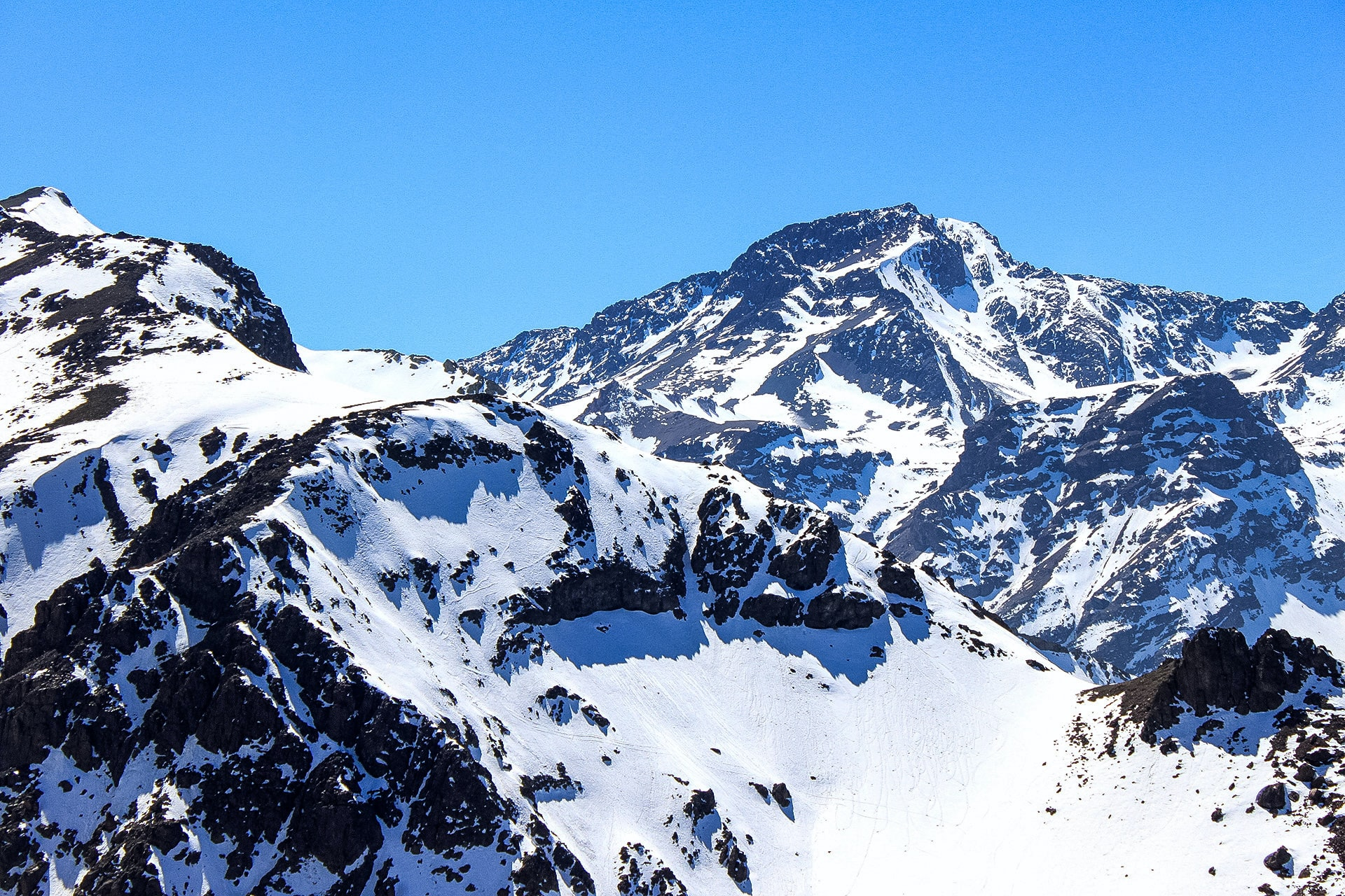 A snowy mountain peak in front of a vivid blue sky