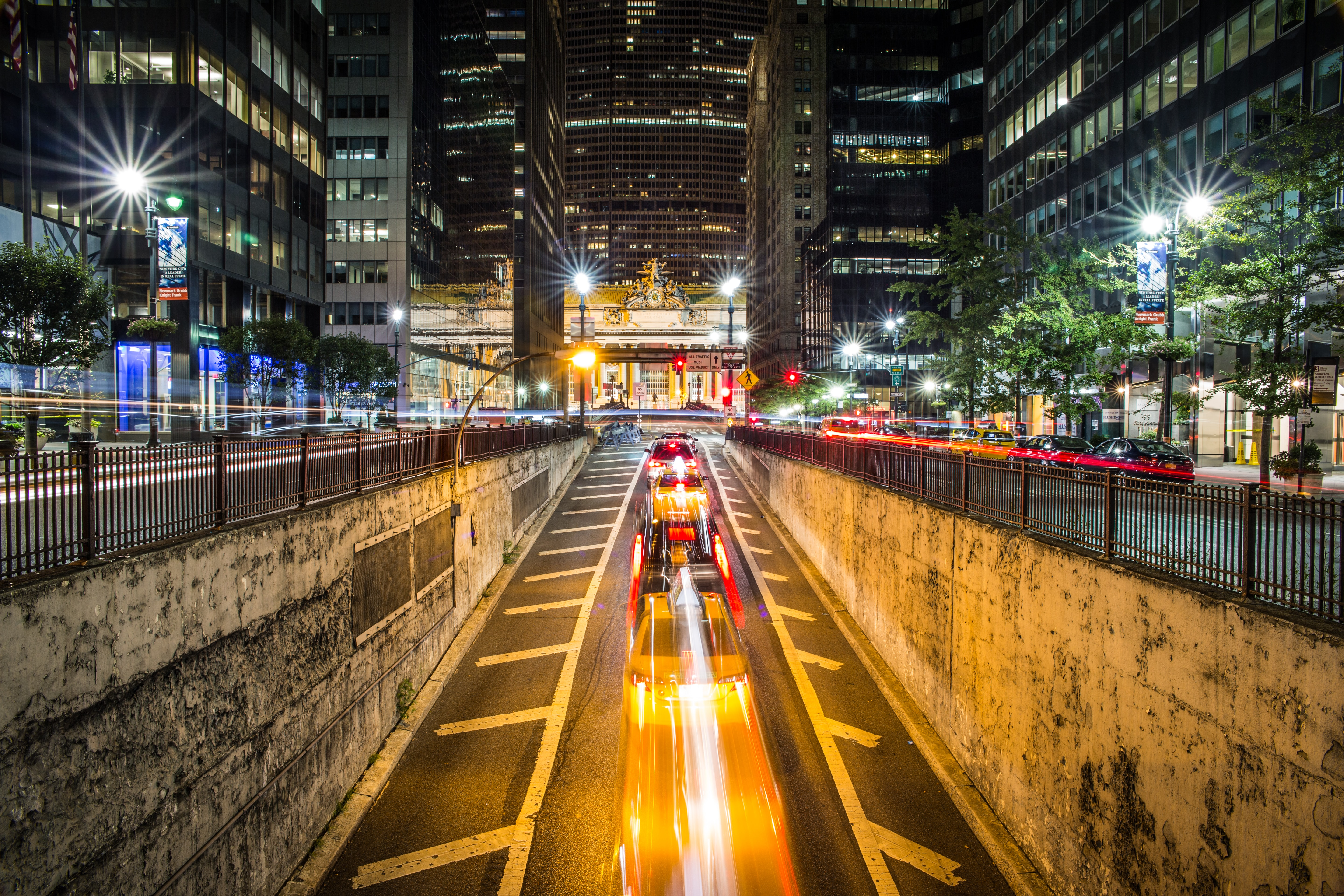 Time lapse shot of New York city center street at night-time surrounded by skyscrapers