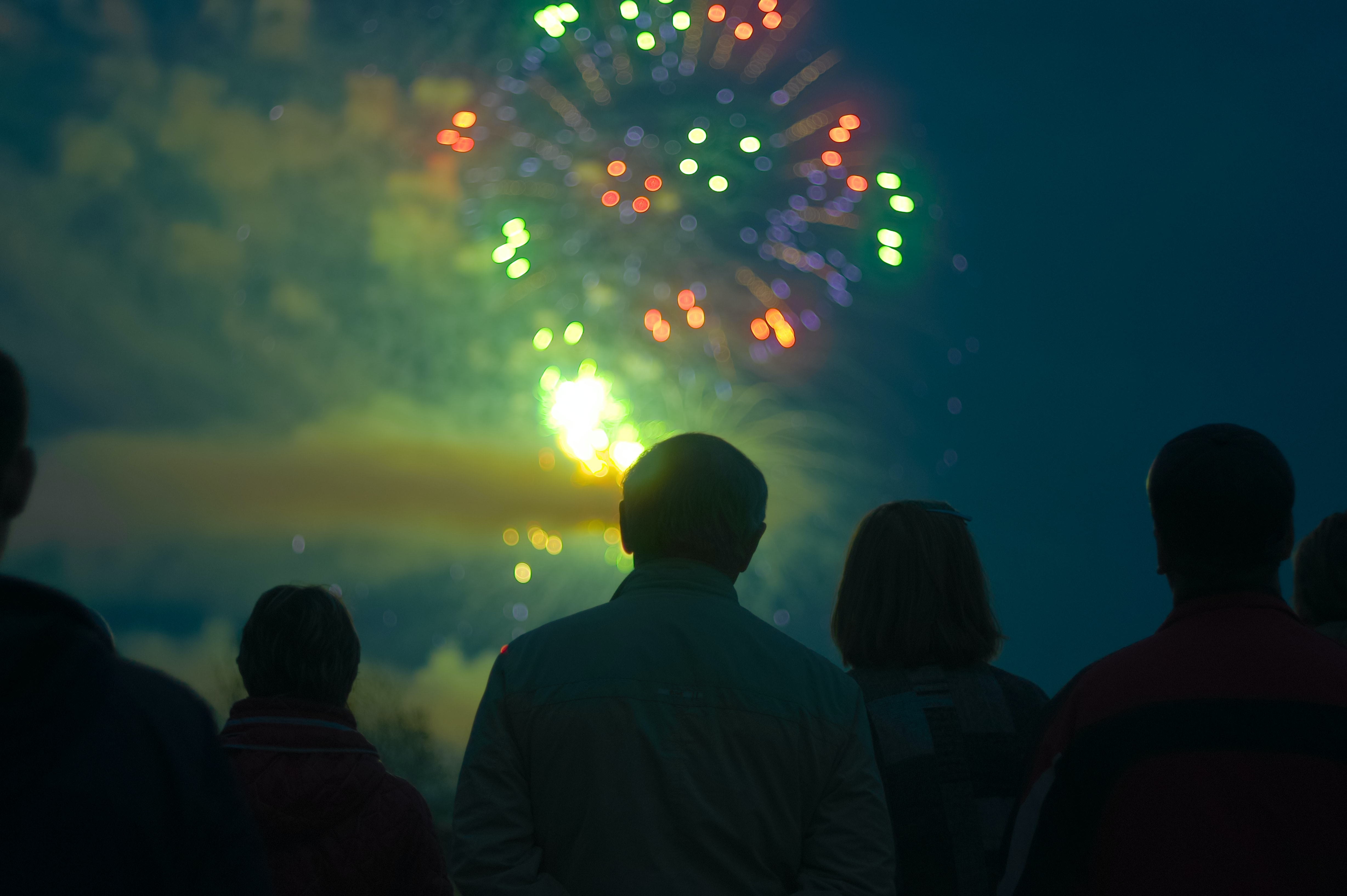 Group of people watching a green and red firework explode
