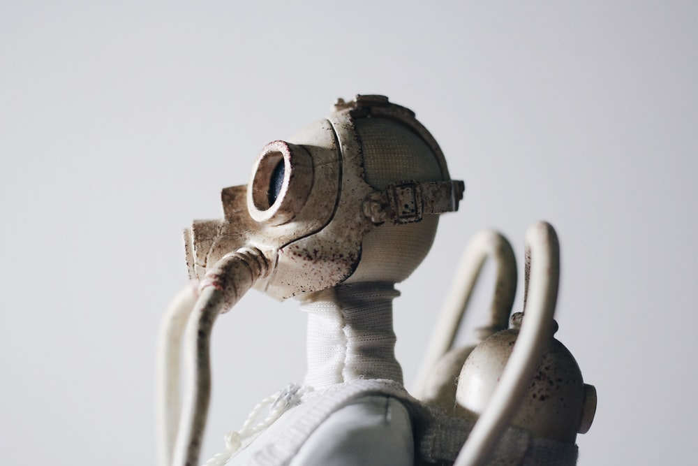 selective focus photography of man wearing gas mask and oxygen tank