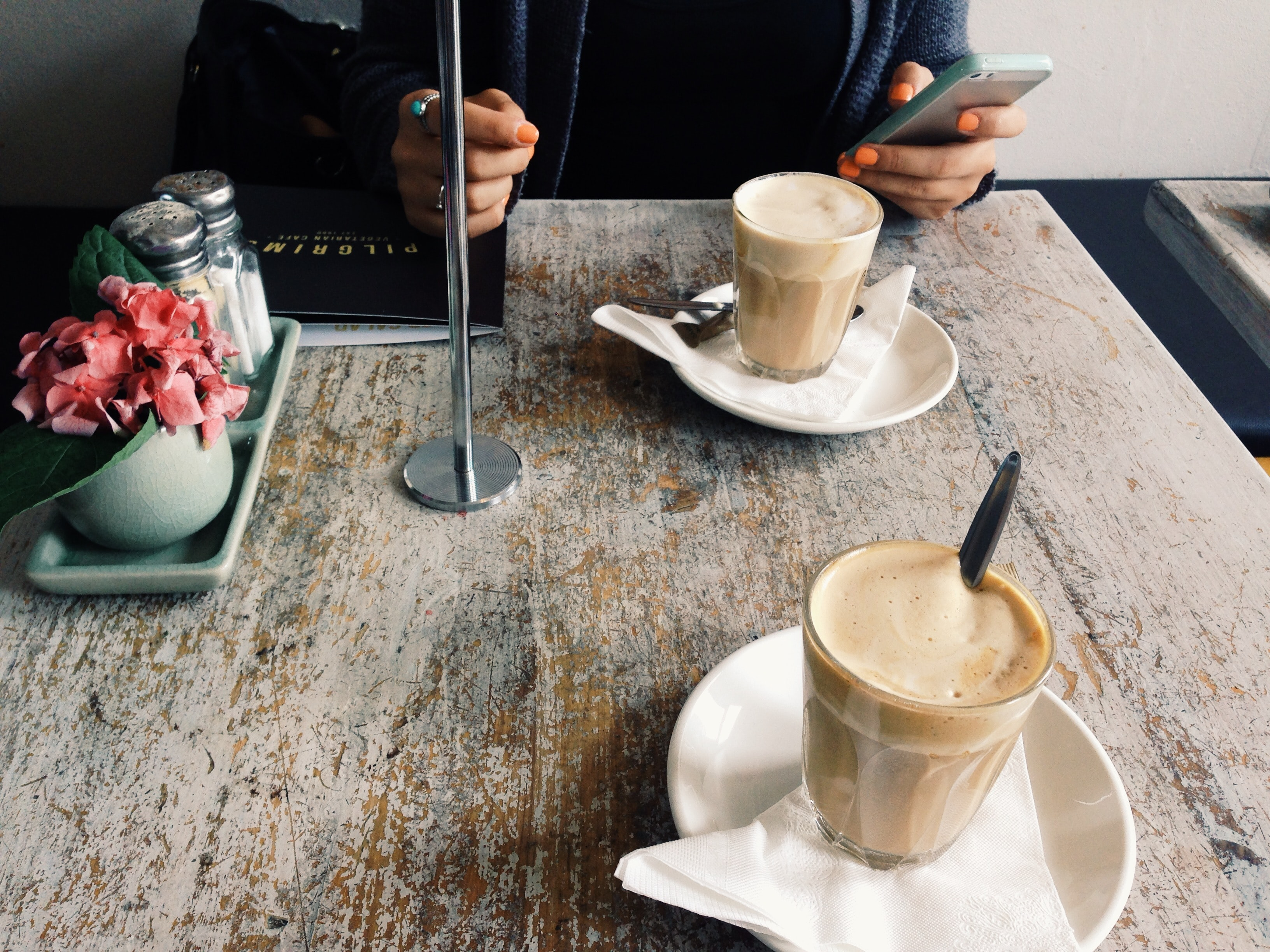 A person with a smartphone in their hand sitting at a table with two cups of latte