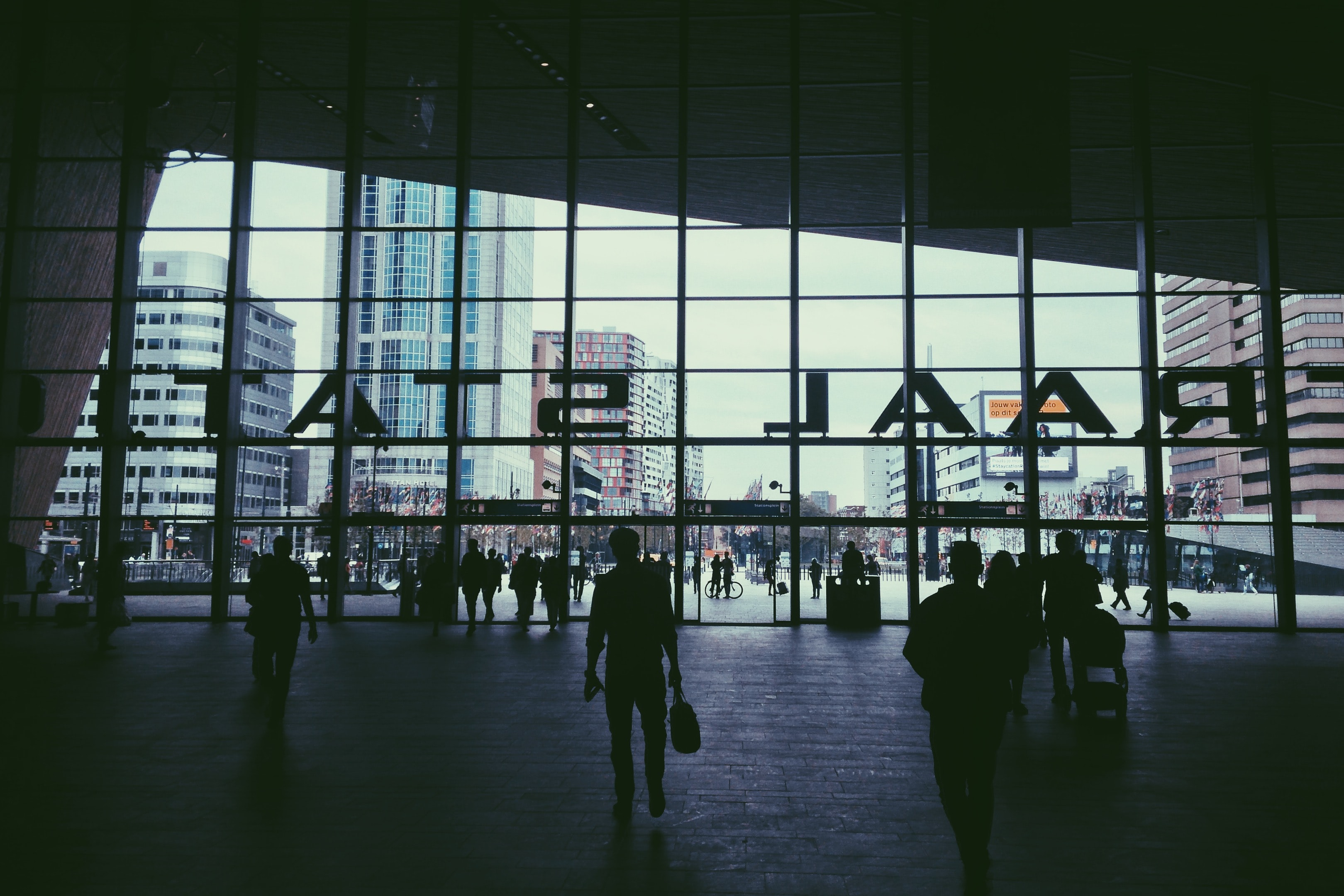 Passengers are at the entrance of the Rotterdam Centraal Station with the Rotterdam cityscape in view.