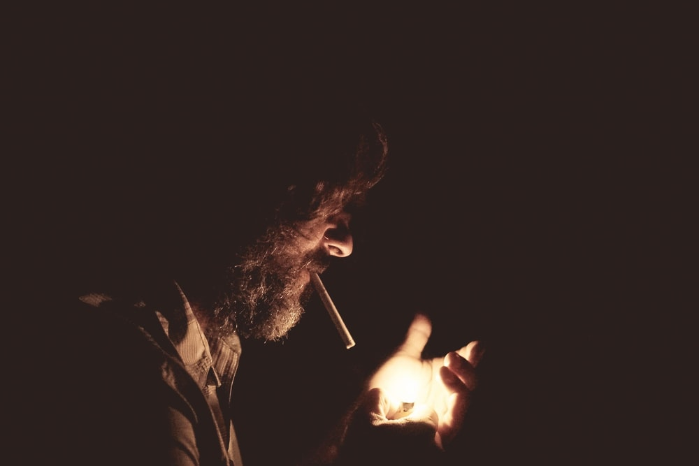 man with cigarette on his mouth holding lighter