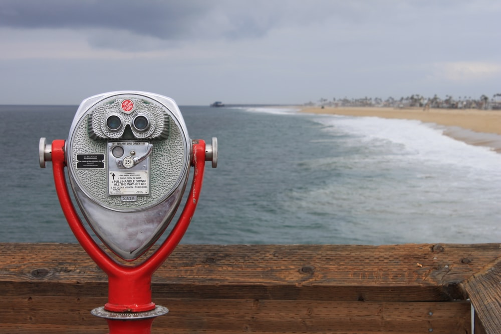 grey and red coin operated binoculars in front of seawaves under nimbus clouds during daytime