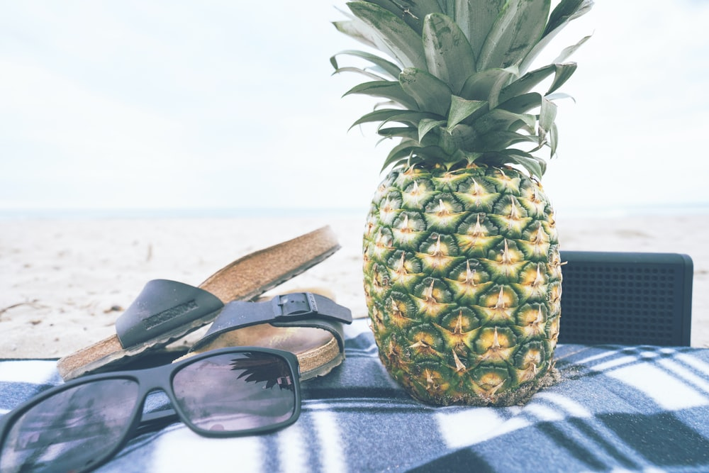 green and yellow pineapple besides black slide slippers and sunglasses