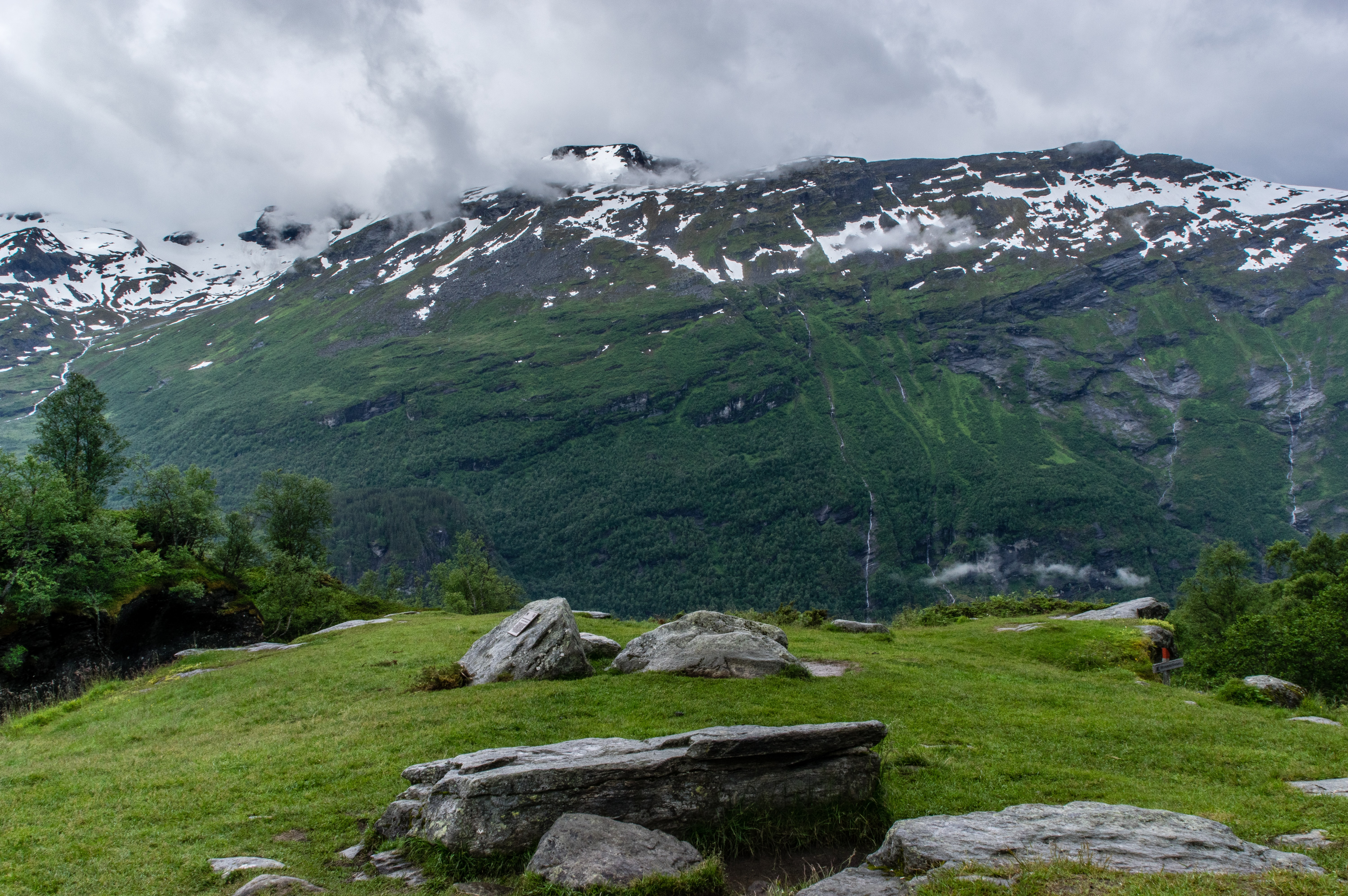View of clouds and snowy mountains from a stony grassy slope in the village of Geiranger