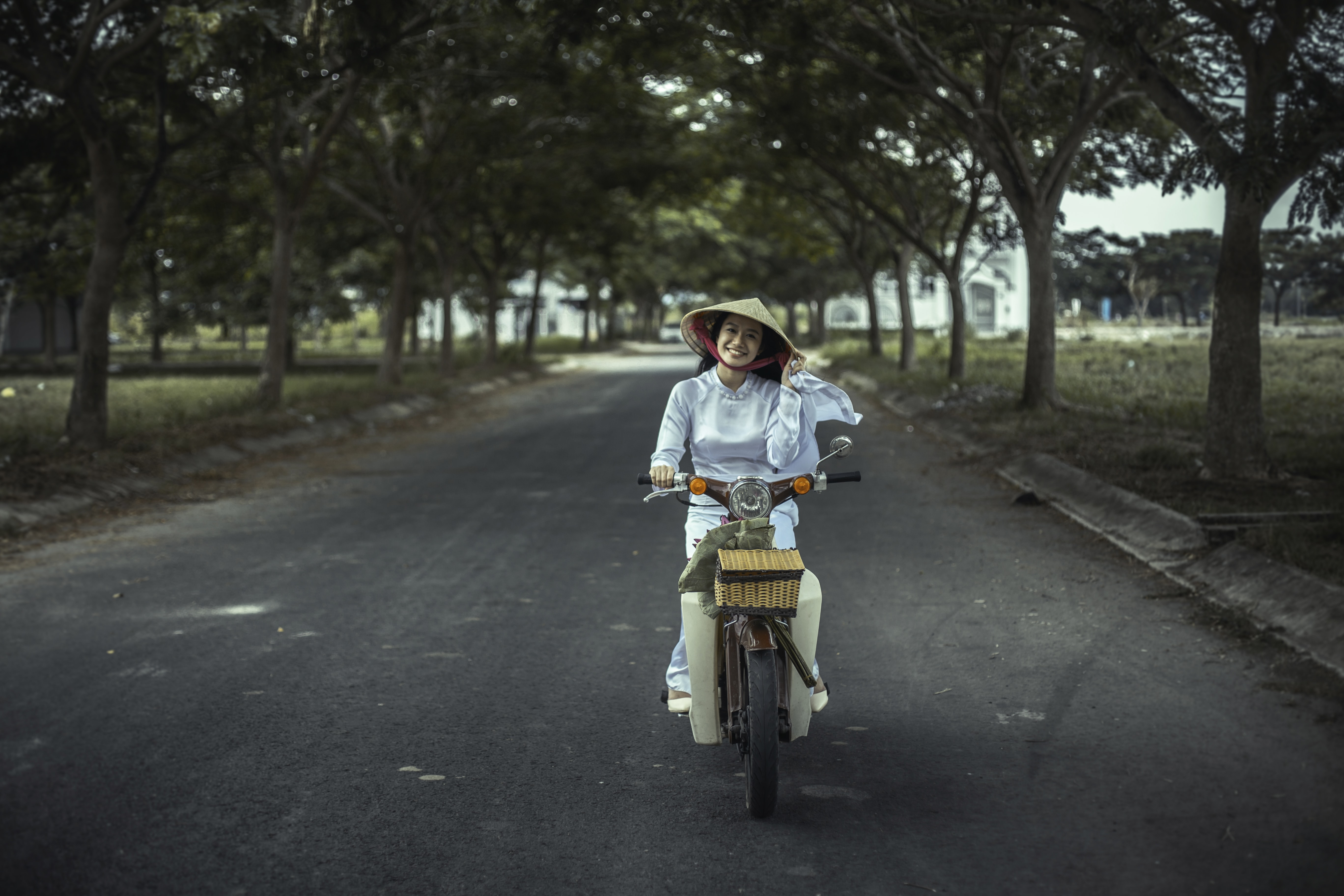 A smiling woman in a rice hat riding a vintage motorbike on a tree-lined road