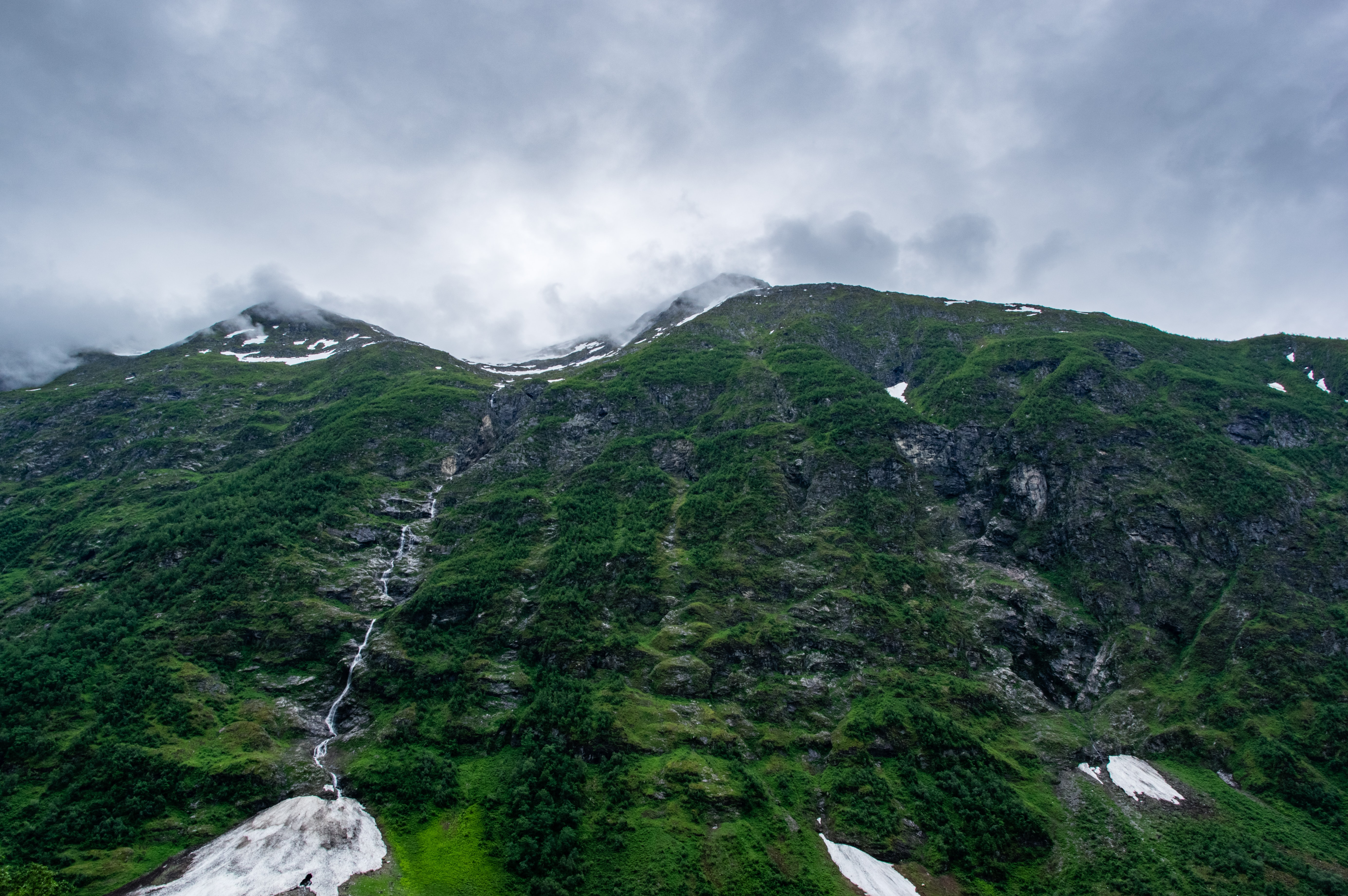 Grassy mountainside with waterfalls in Geiranger