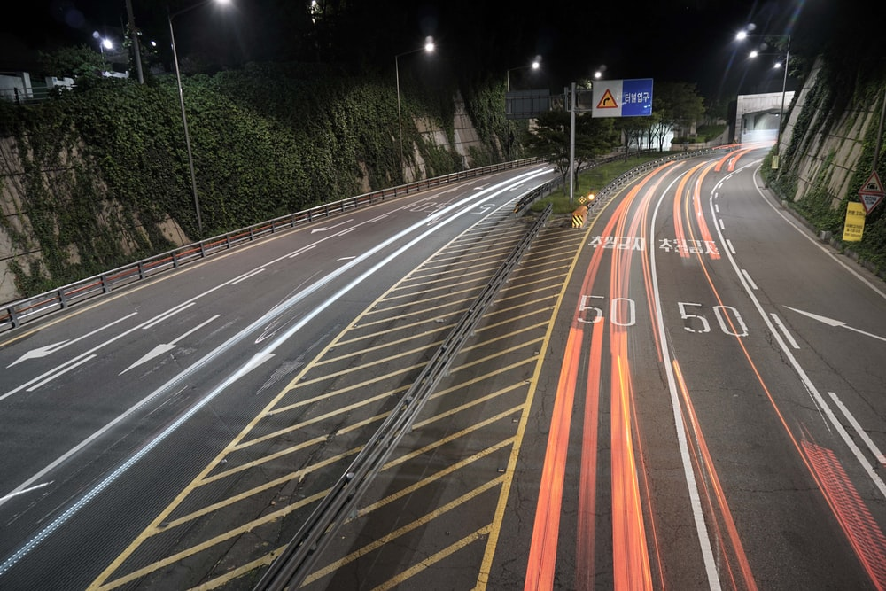 concrete road with street lights during nighttime
