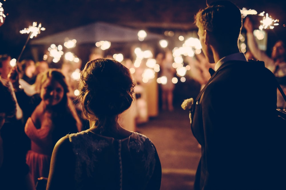 man standing near the woman walking in party during nighttime