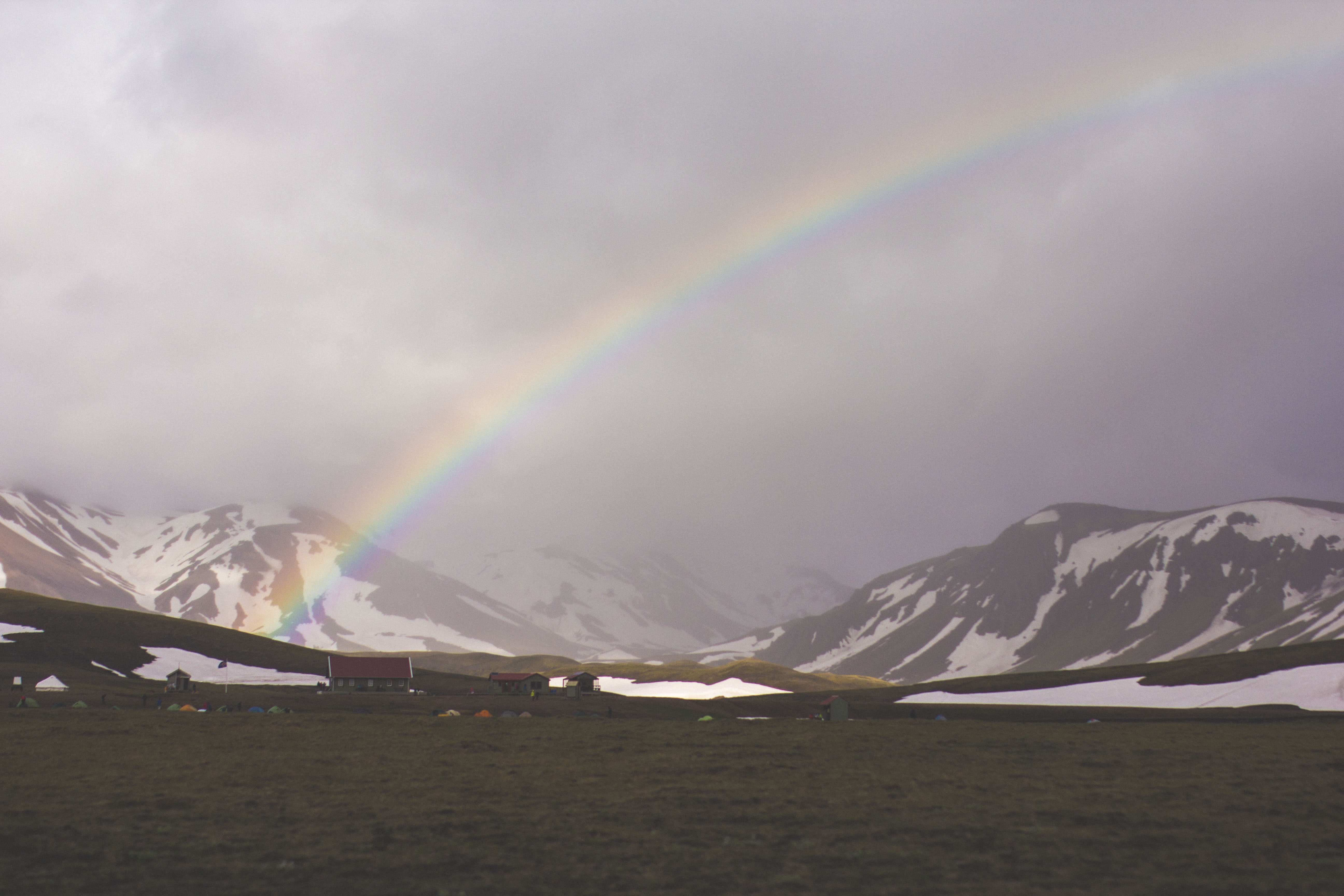 A landscape of rainbow over a field with a view of mountains covered in snow