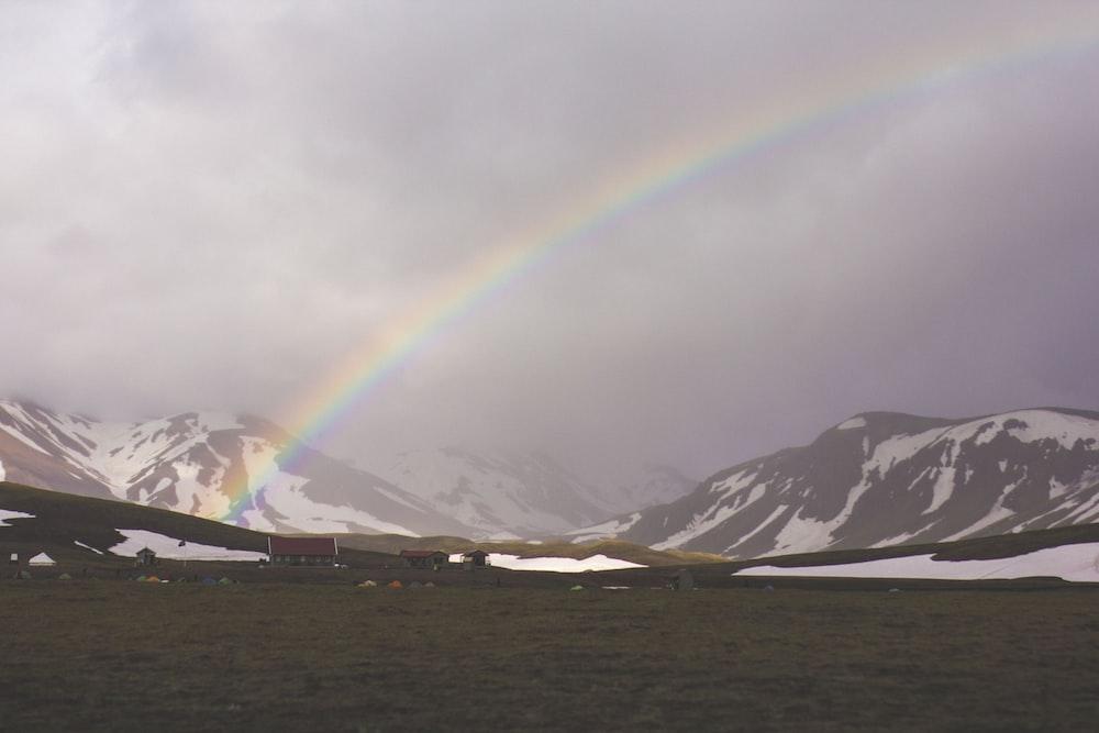 gray mountain near body of water under white rainbow