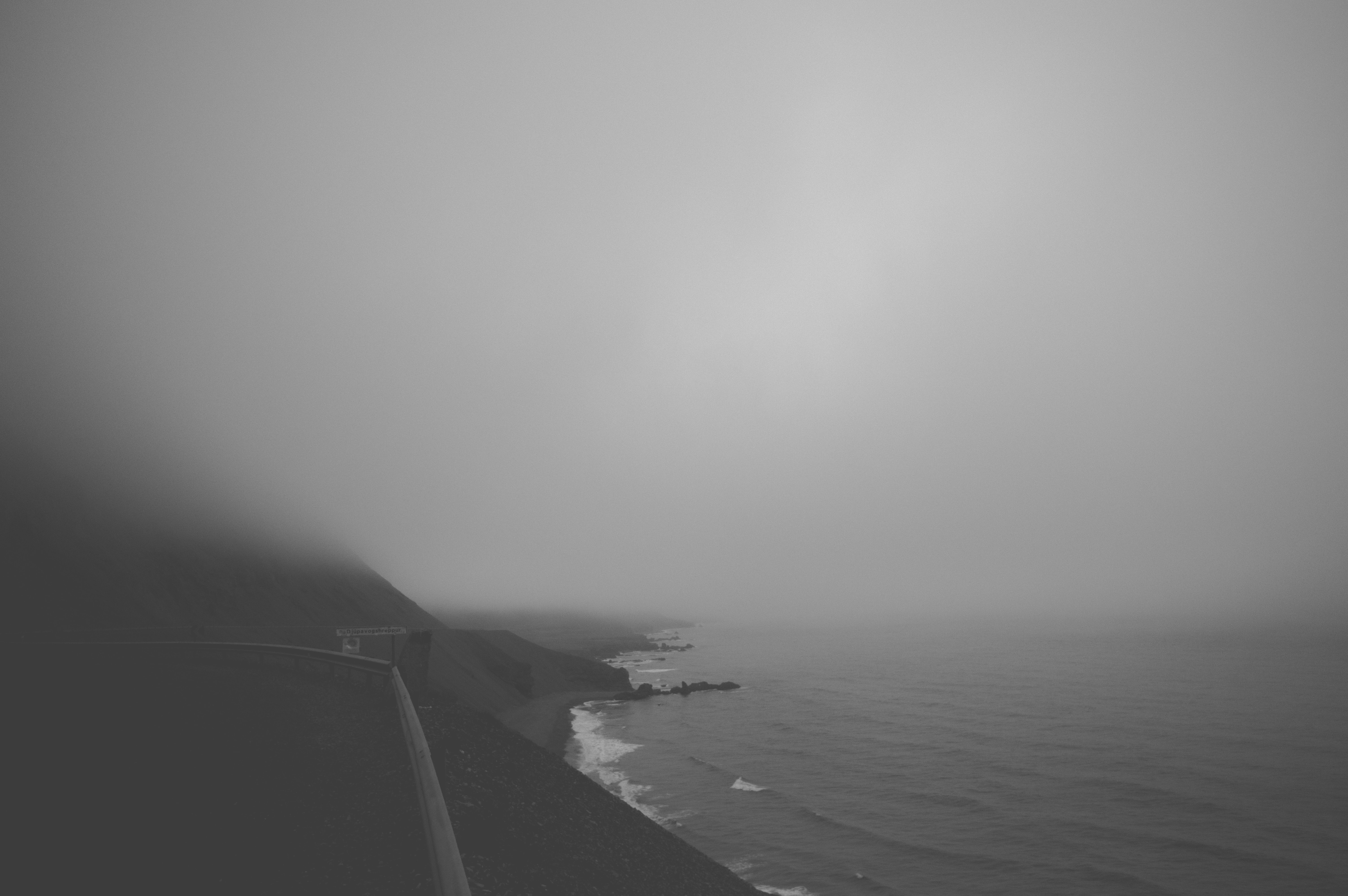 Monochromatic mist covers the seashore and beach below