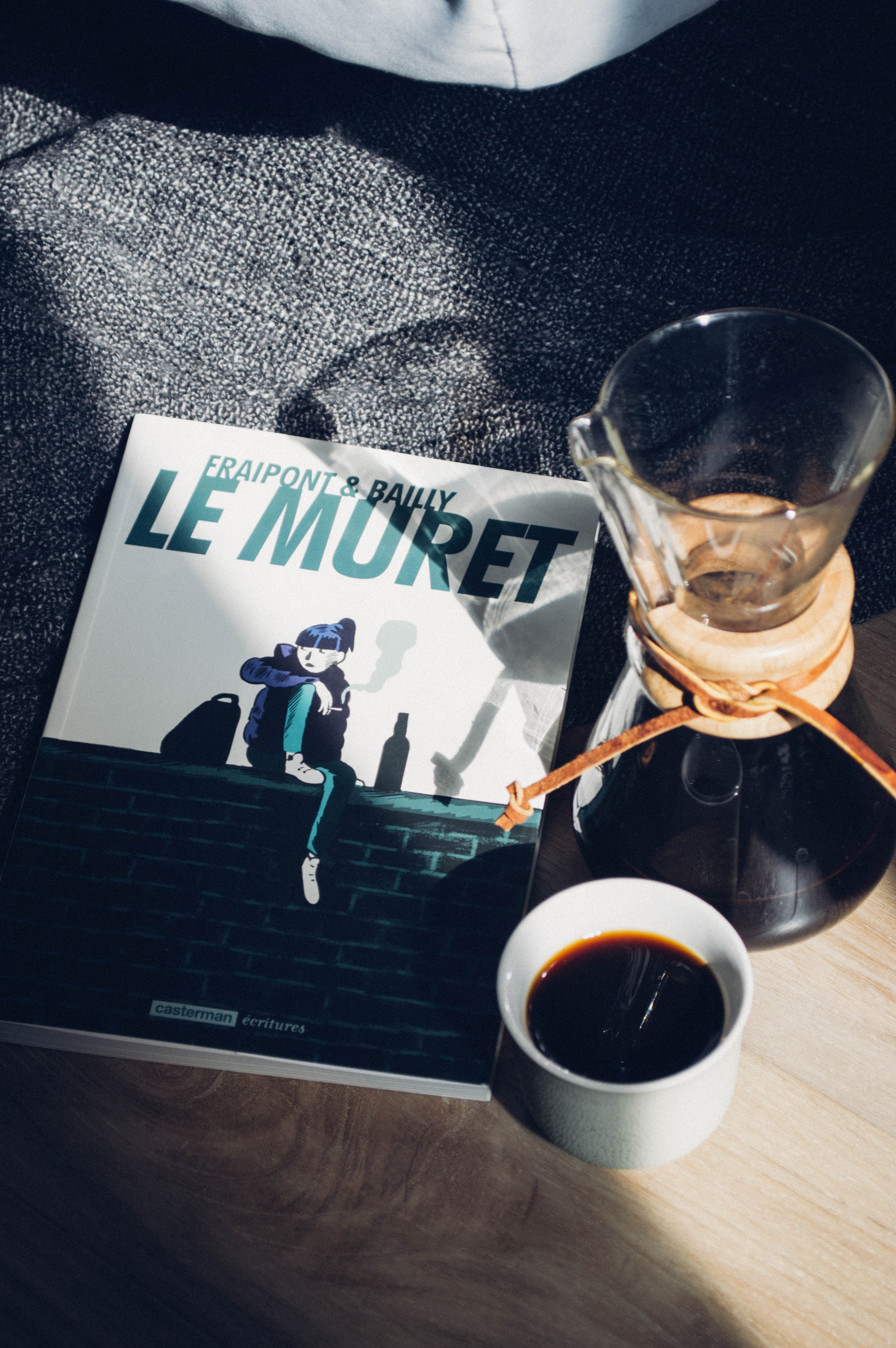 A cup of coffee and Chemex sit on a wood surface aside a book