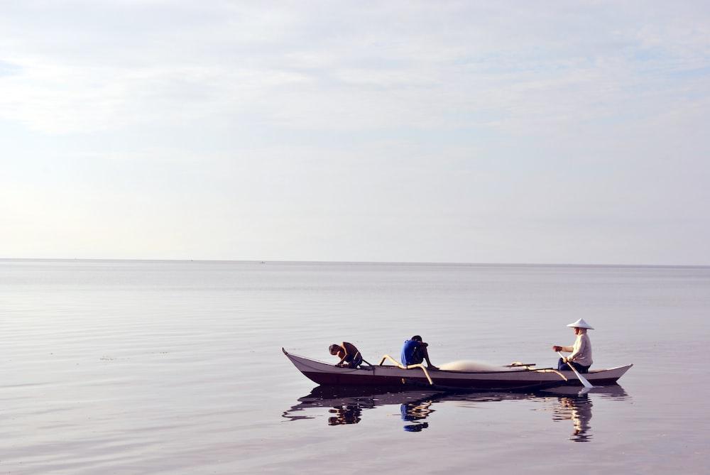 three person riding canoe at sea