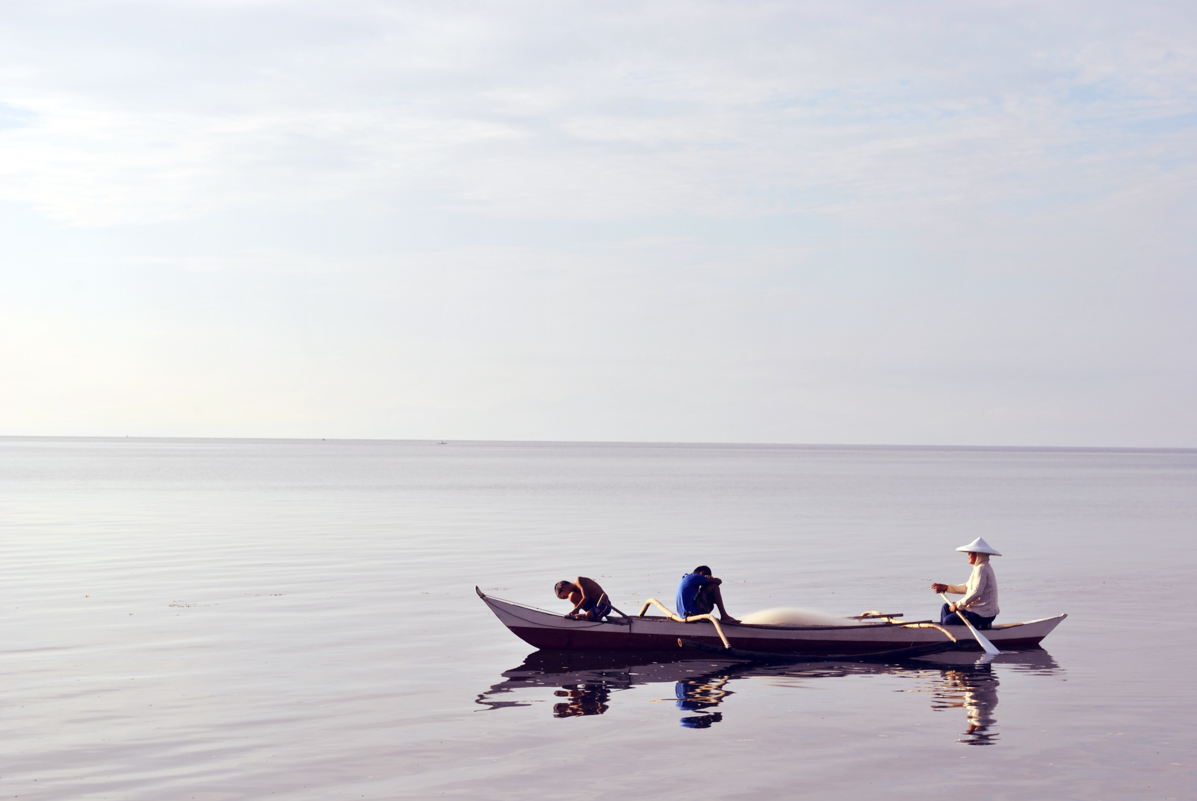 Two kids and a woman on a canoe in the sea in Merida