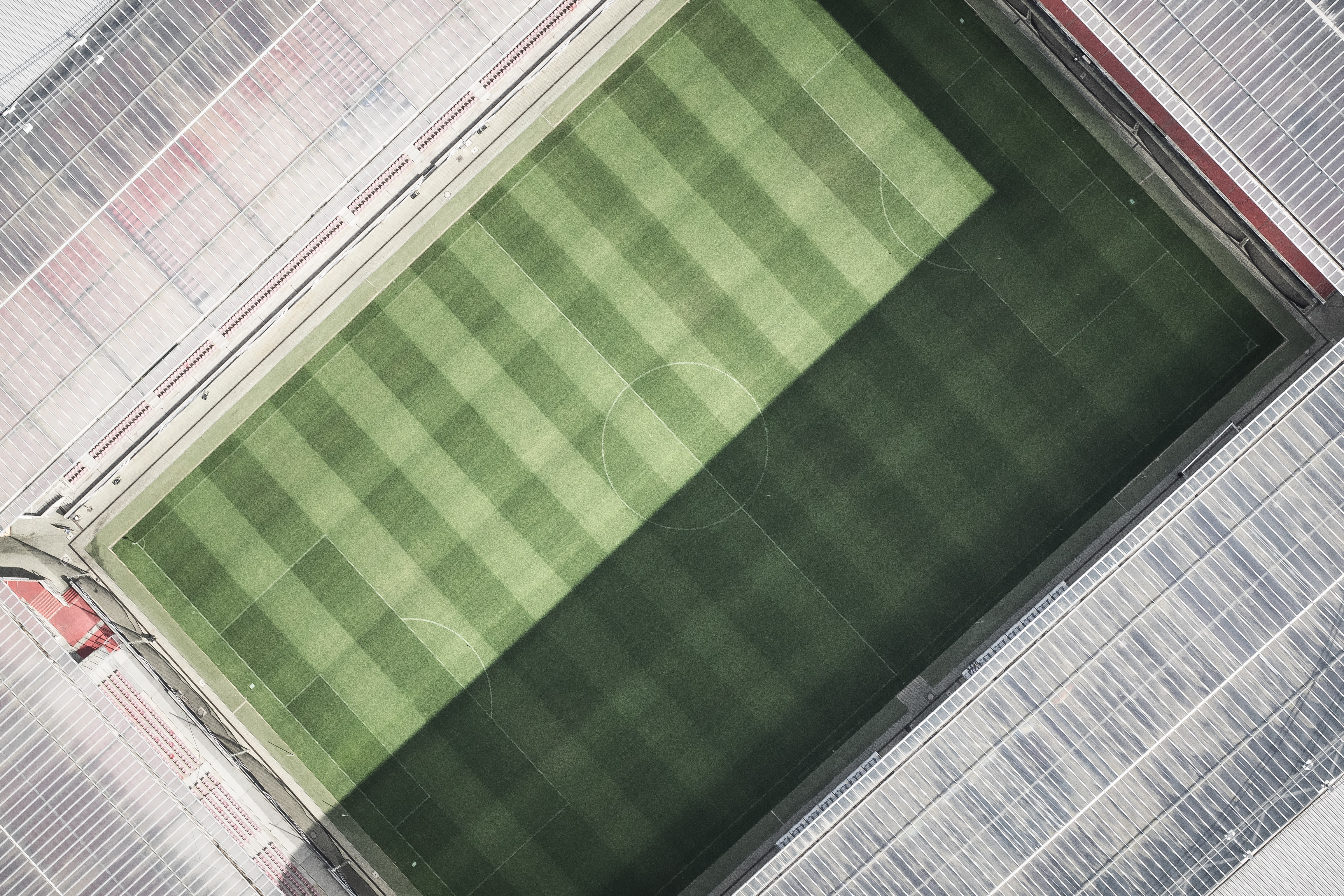 Drone aerial view of a soccer stadium pitch and roof.