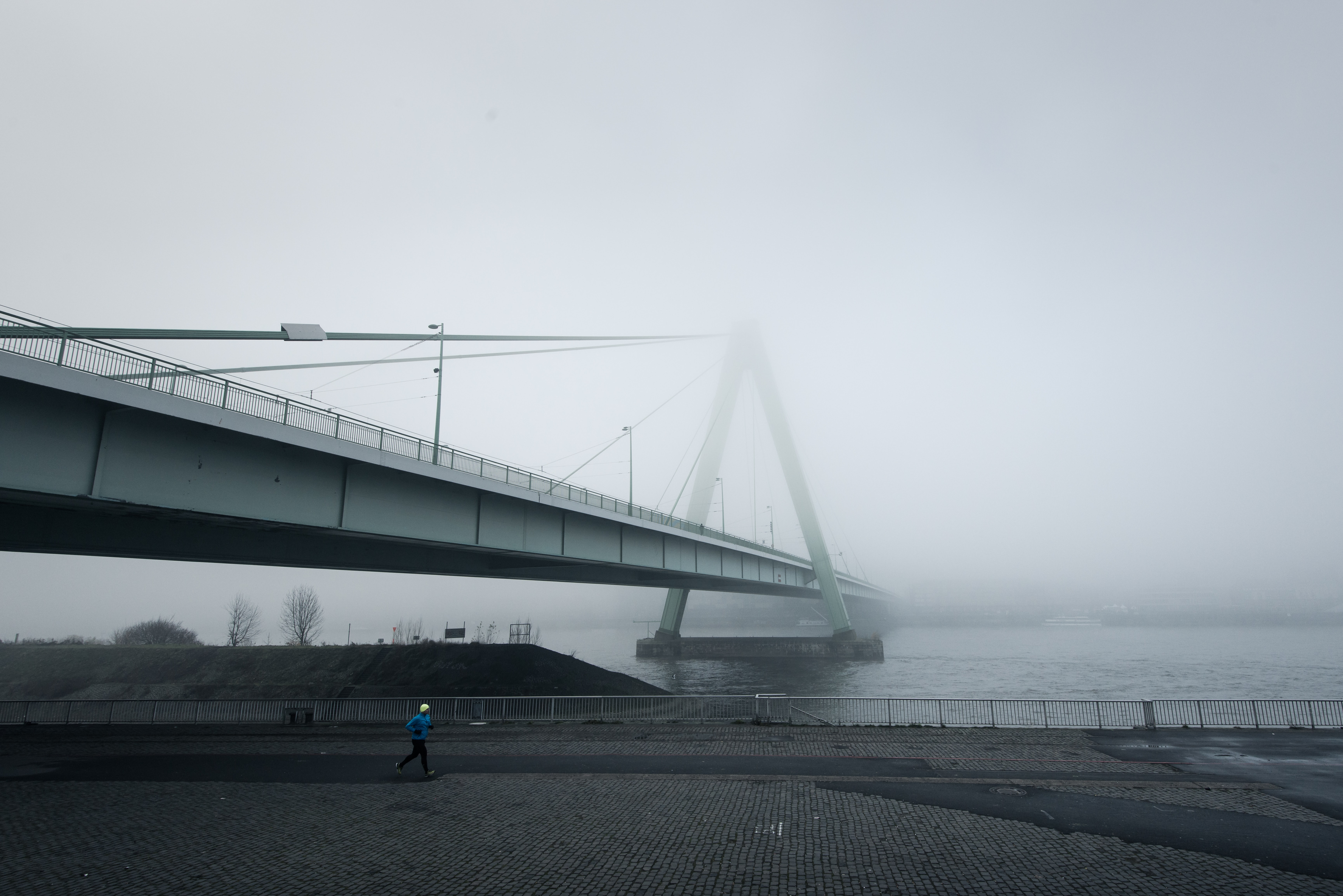 A view of a suspension bridge on a foggy, misty day