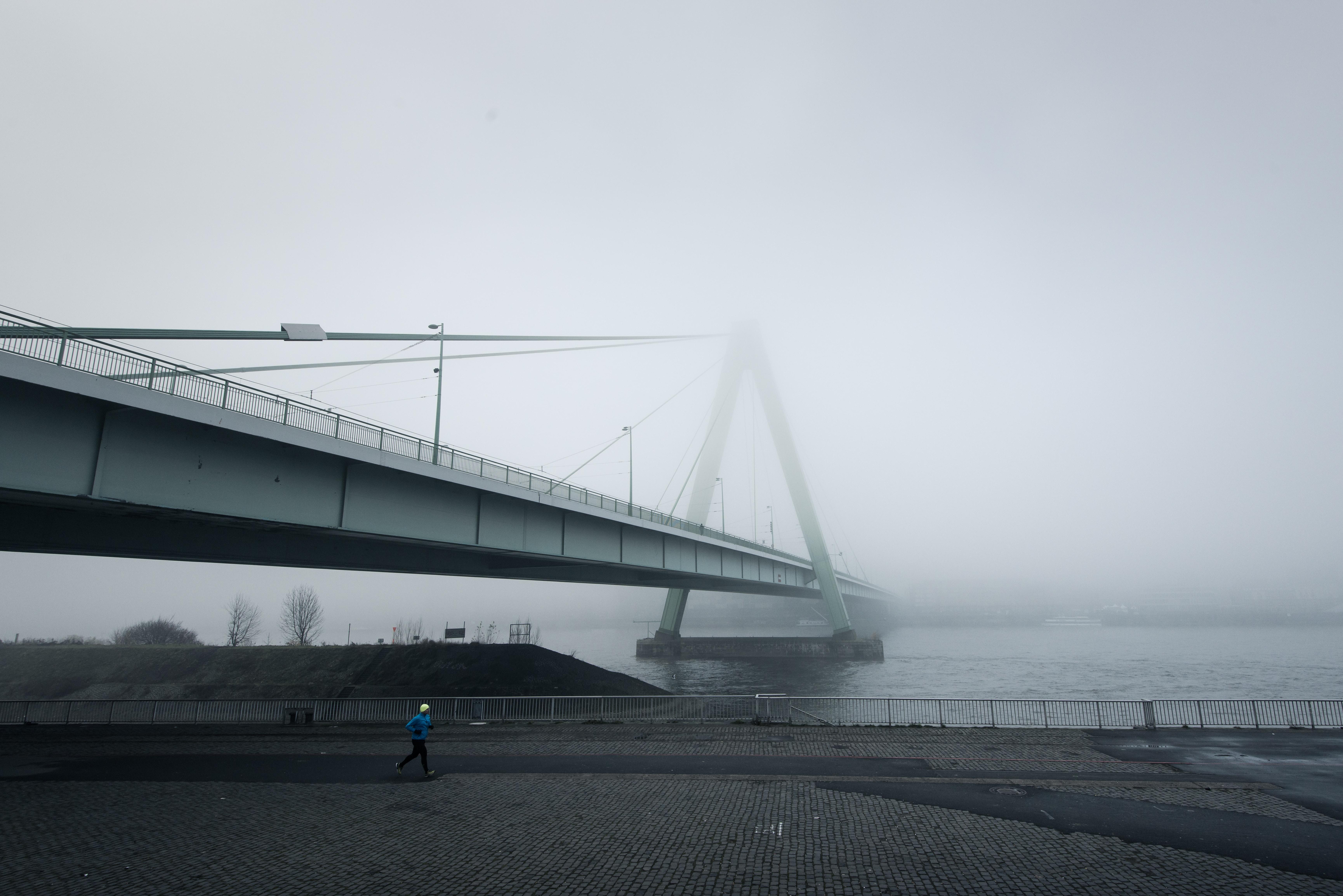 person jogging under bridge during dawn
