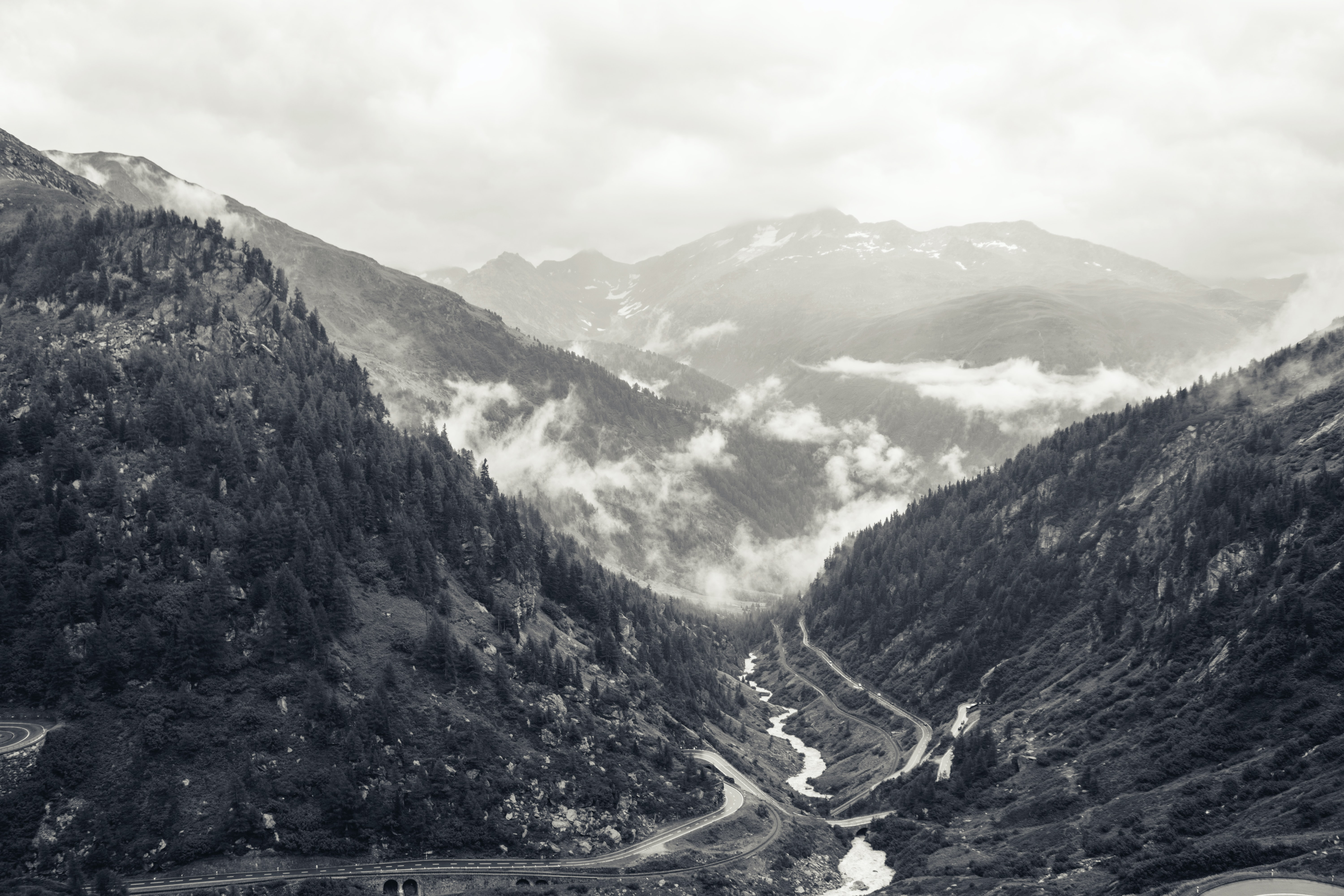 A desaturated shot of clouds of fog over a small river in a mountain pass