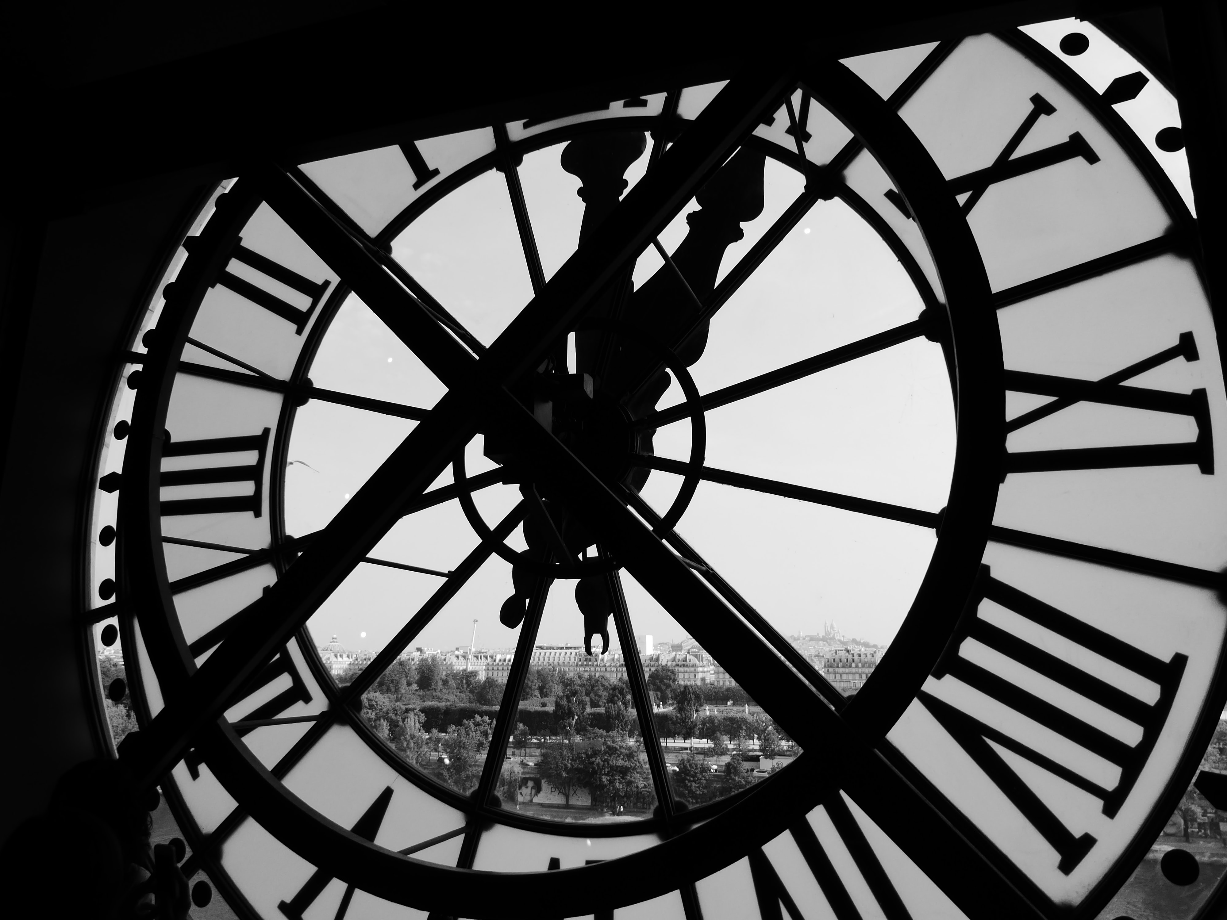 A black and white shot from behind a clock looking out into Paris