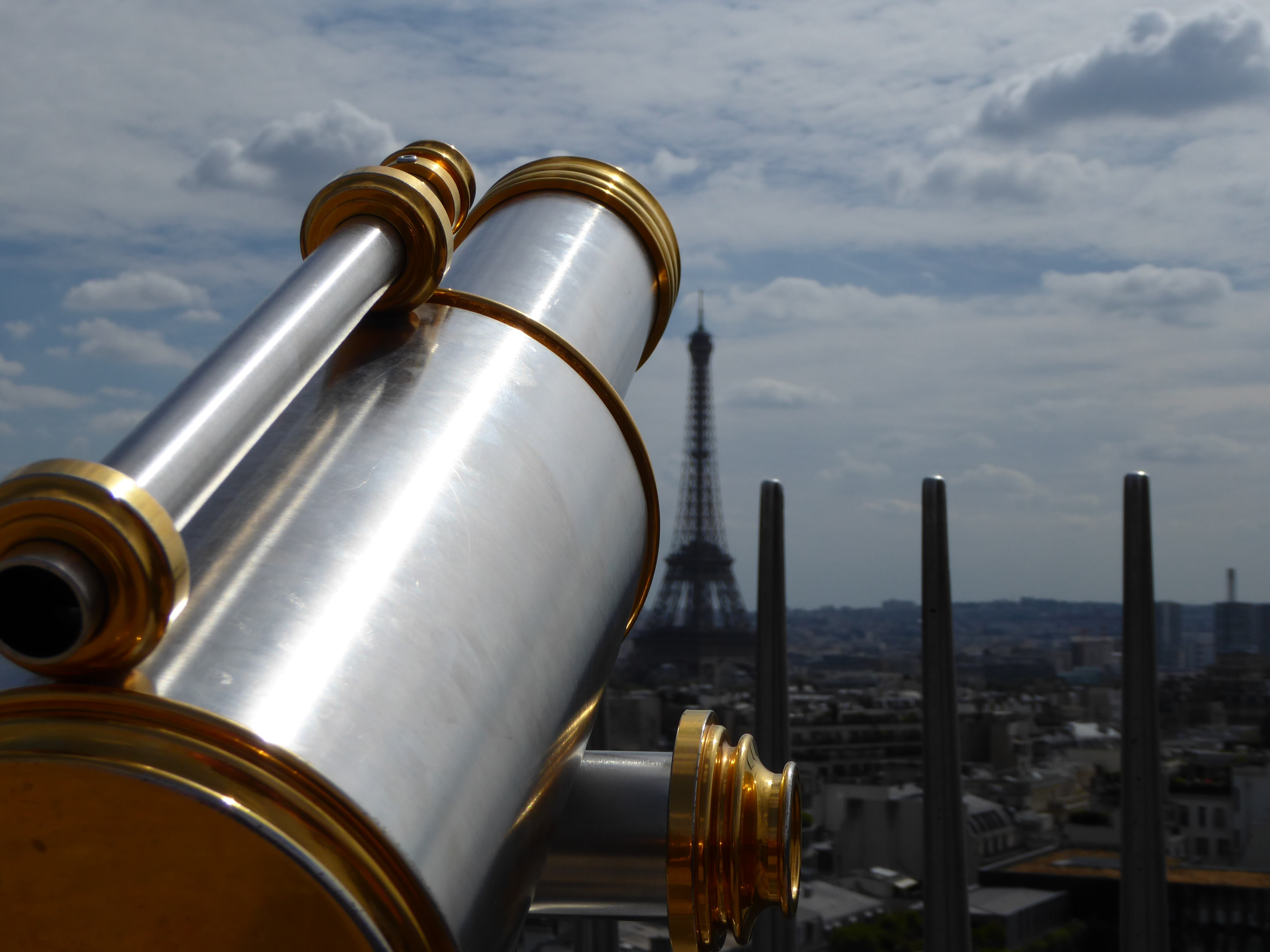A metal viewfinder telescope with the historic Eiffel Tower and Paris cityscape in the background.