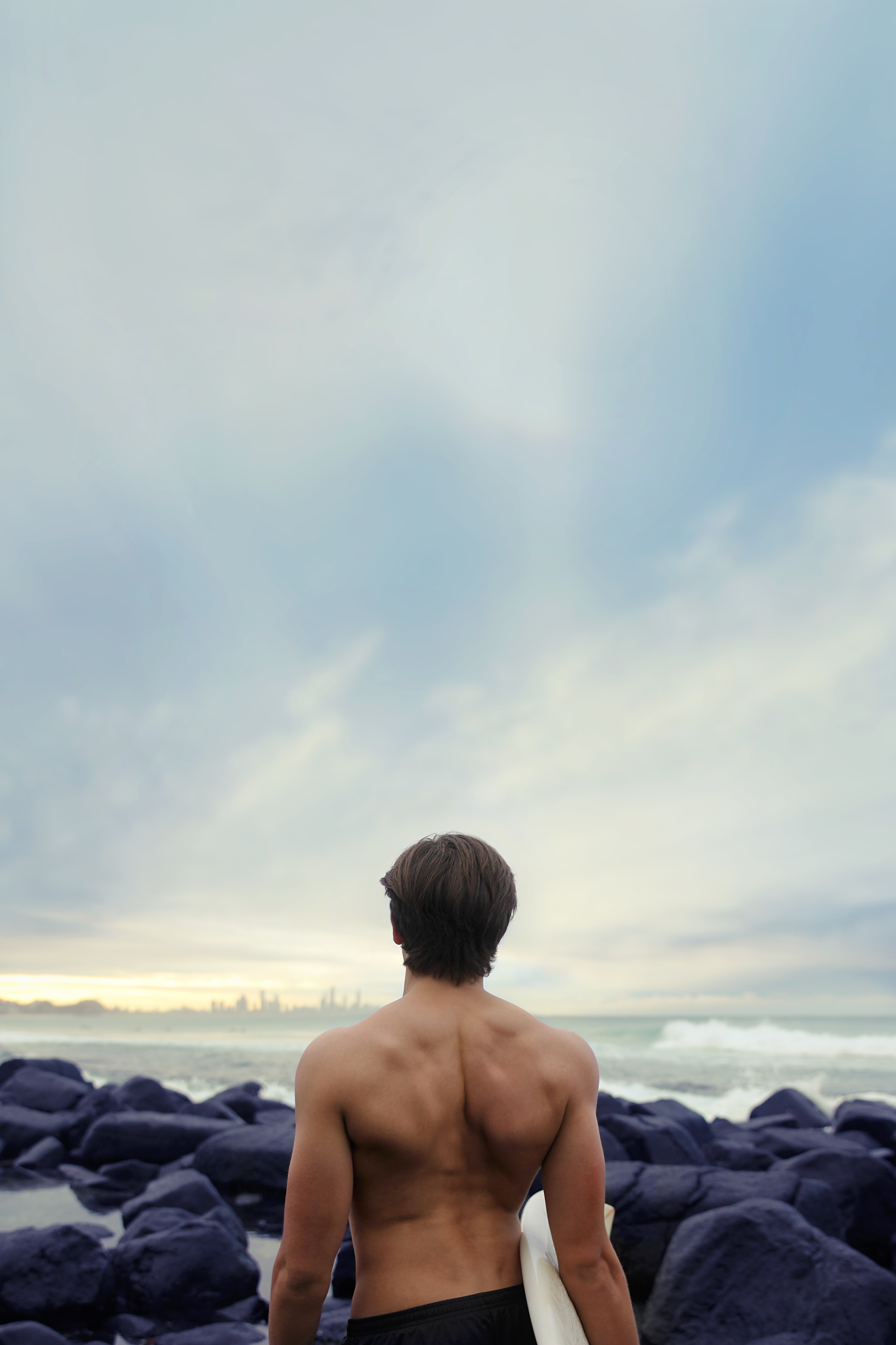 Topless man standing among coastal rocks looking in the distance at Burleigh Beach