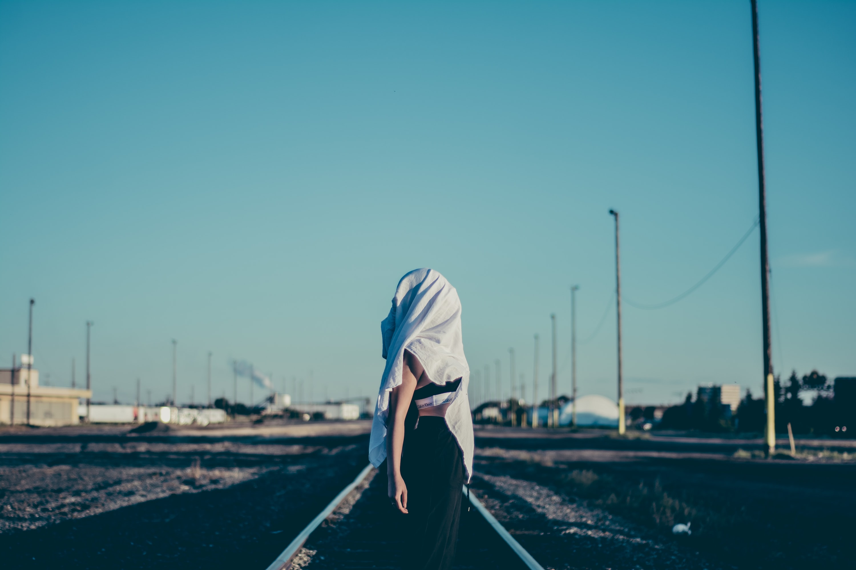 Girl standing on railway tracks in Edmonton with her head covered with a white sheet