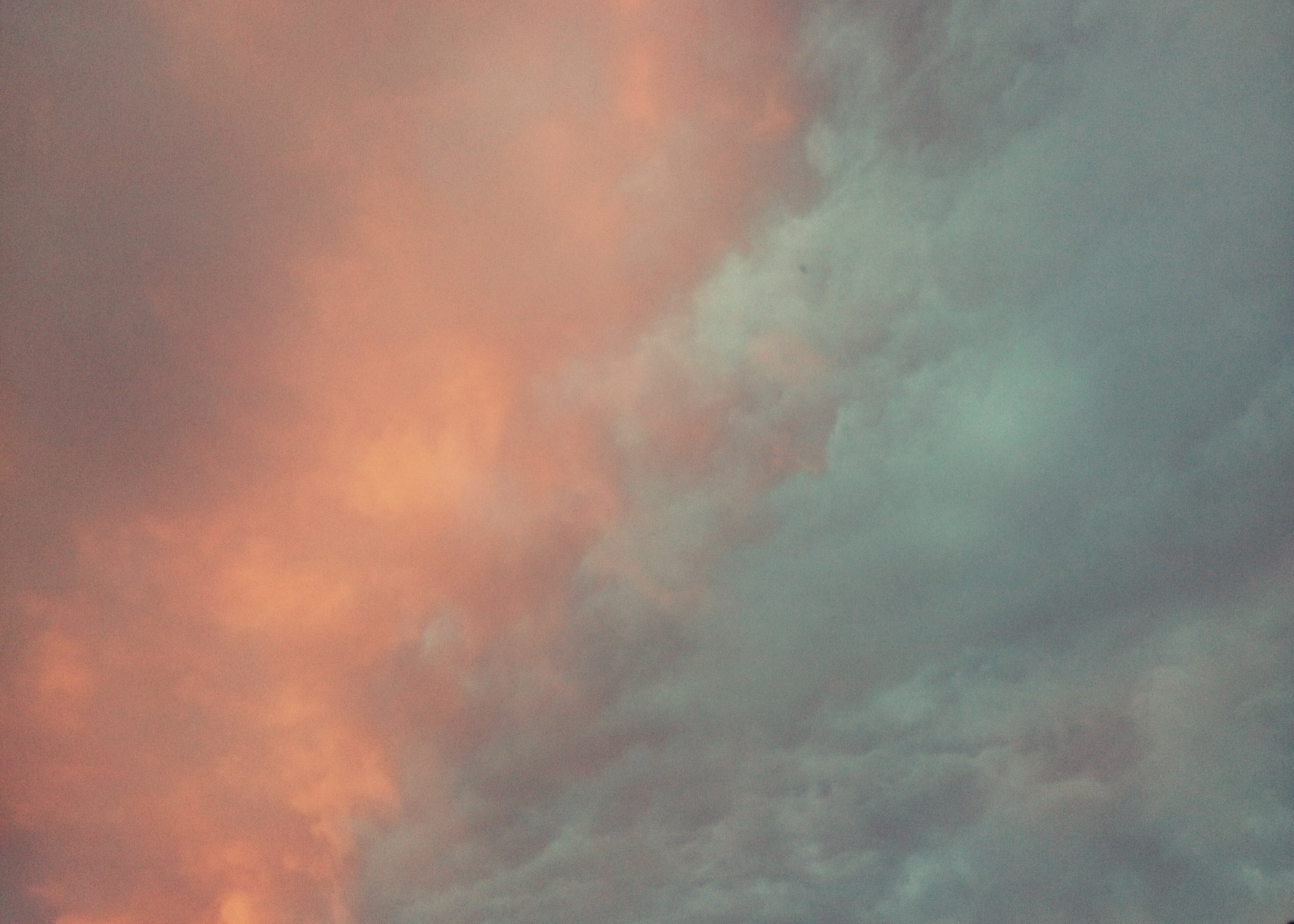 Orange and bluish green clouds in the sky.