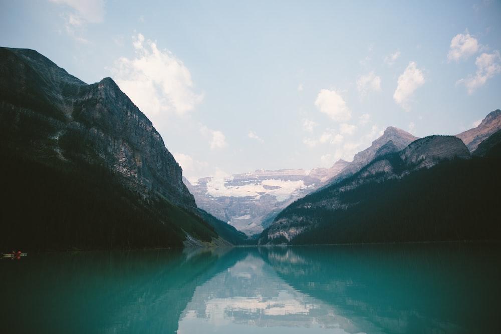 mountain range near body of water under blue skies