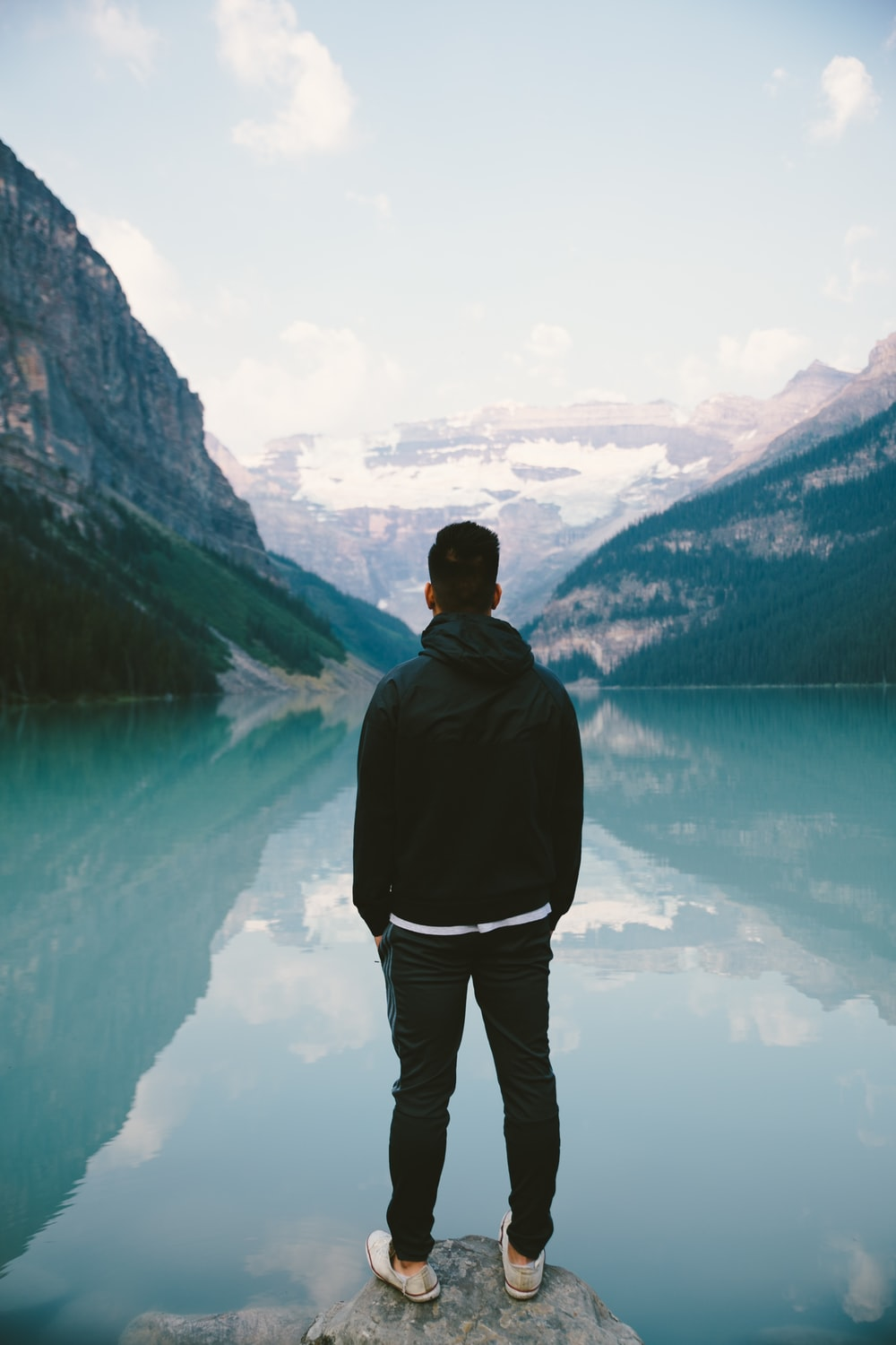 man standing in the middle rock facing lake