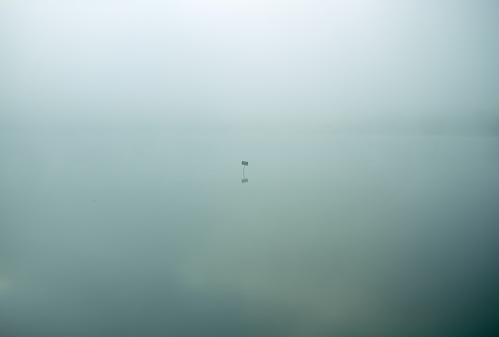 Single isolated sign sits in eerie still waters covered in clouds