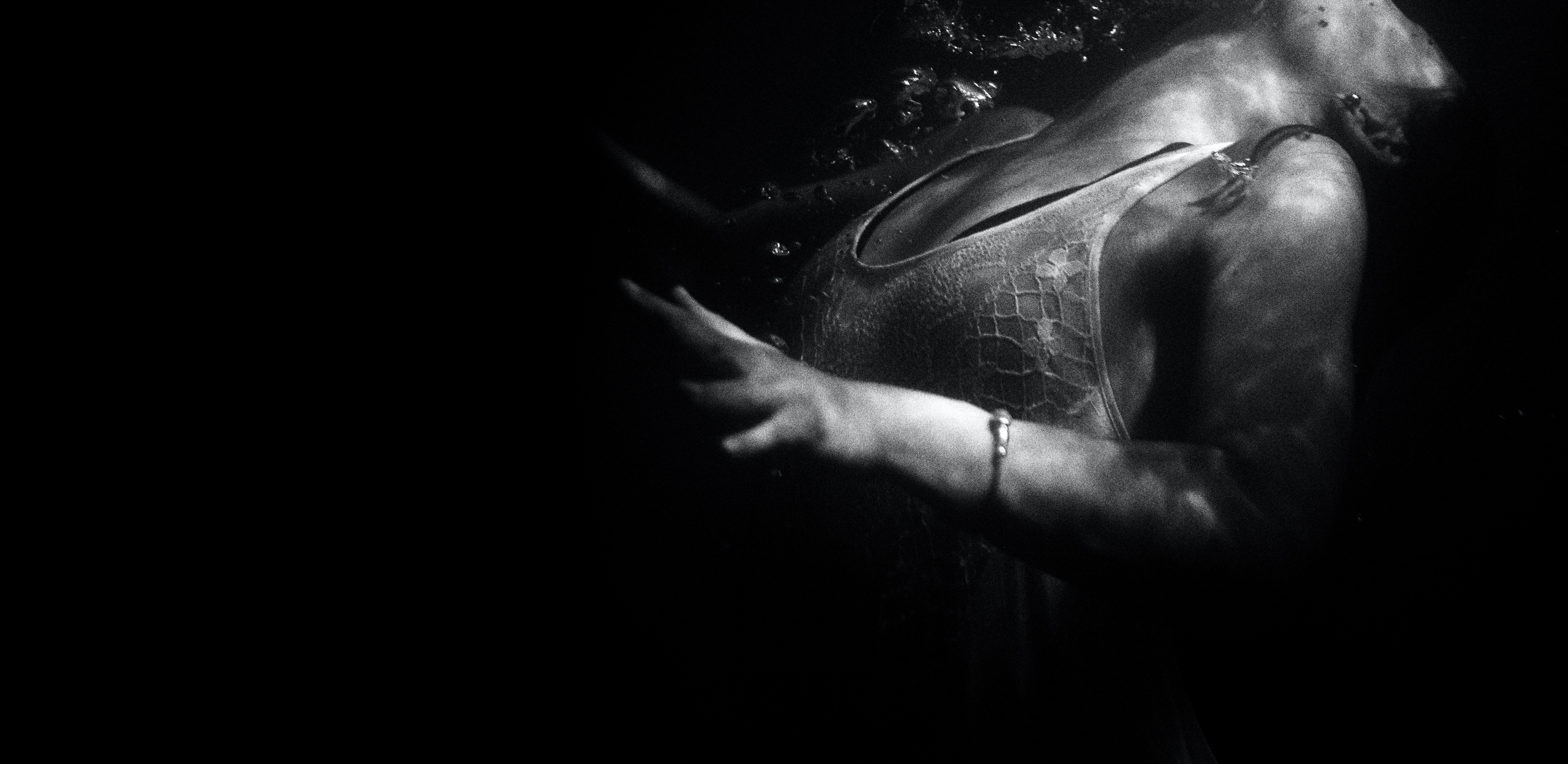 Black and white underwater picture of woman hand and body submerged, Tallebudgera Creek