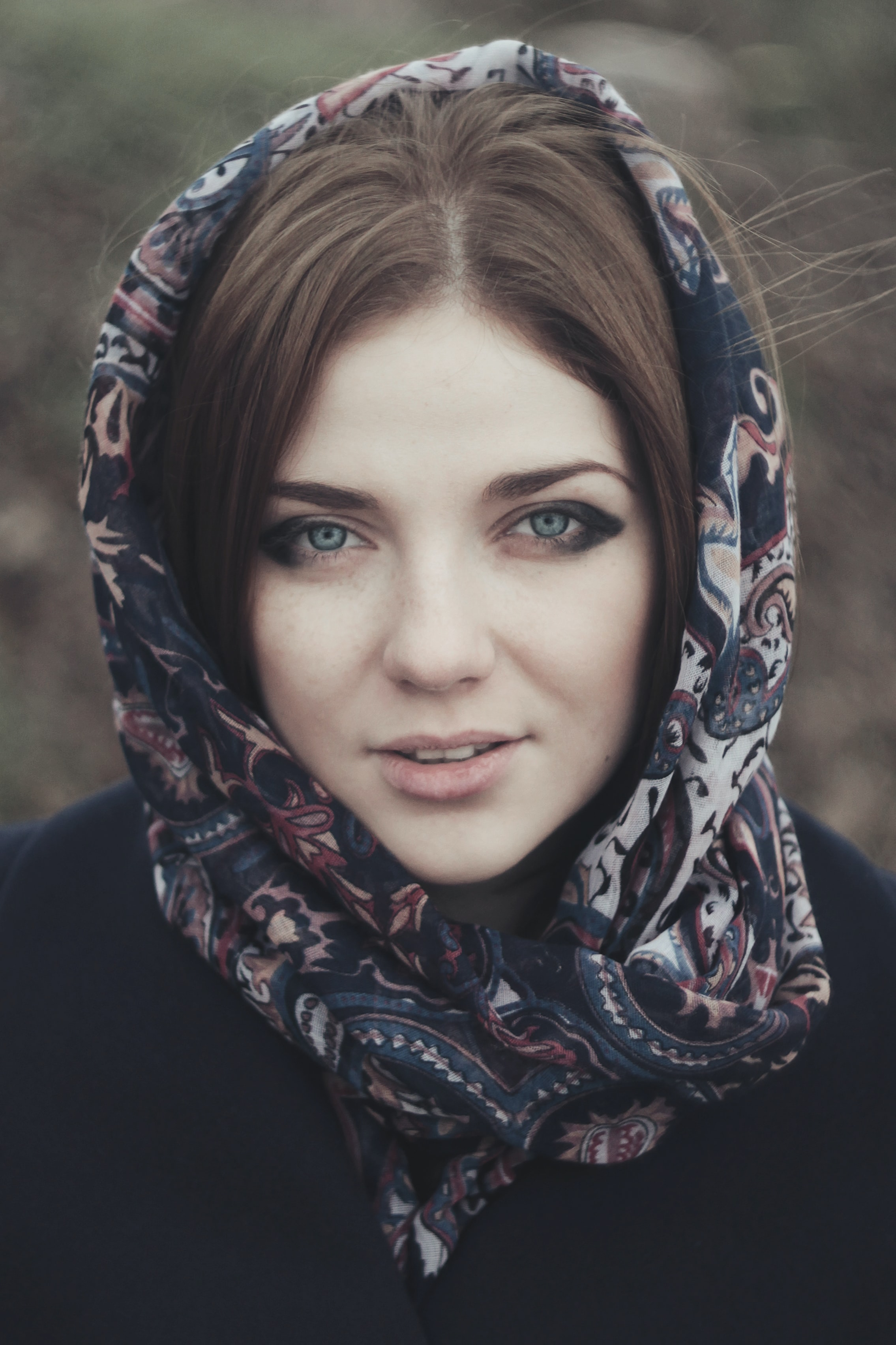 Woman with head wrapped in a scarf smiling