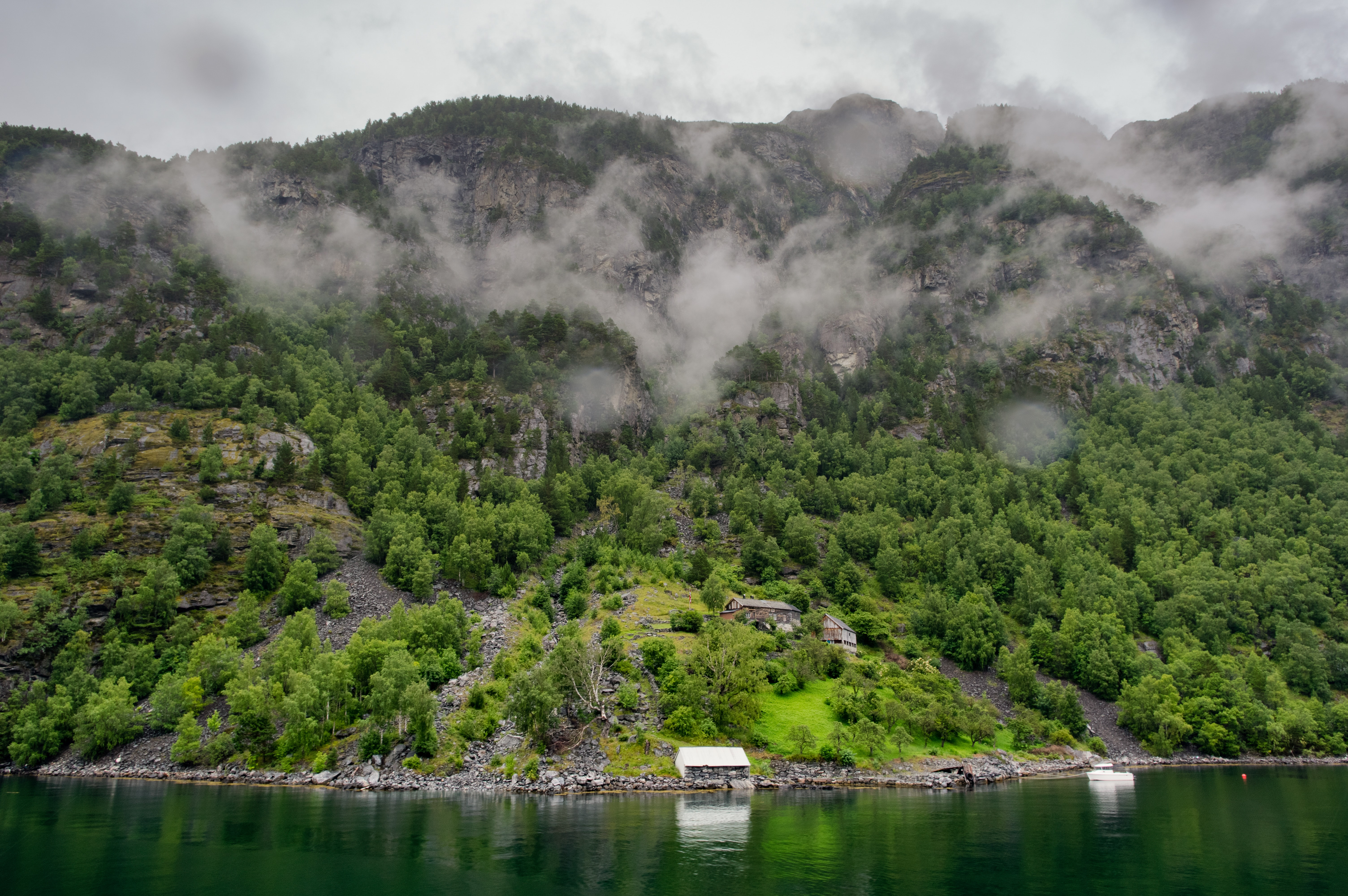 Small white house at the base of a hill with clouds at the top situated on the edge of a lake
