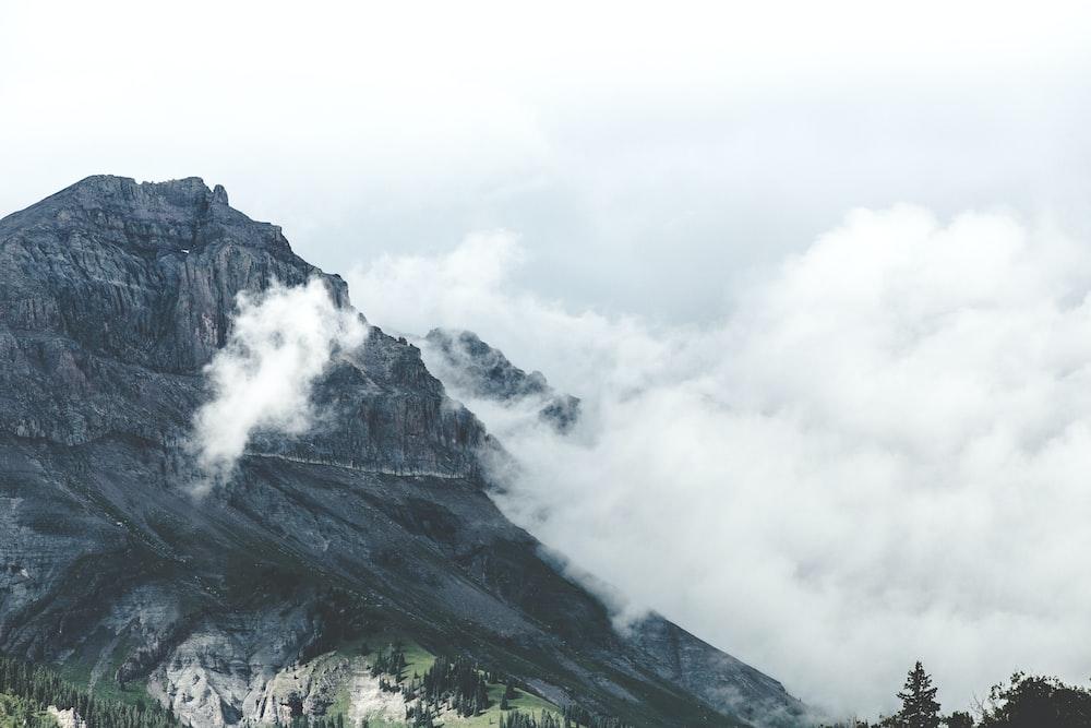 white smoke above gray mountain at daytime