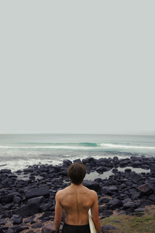 man holding surfboard near sea