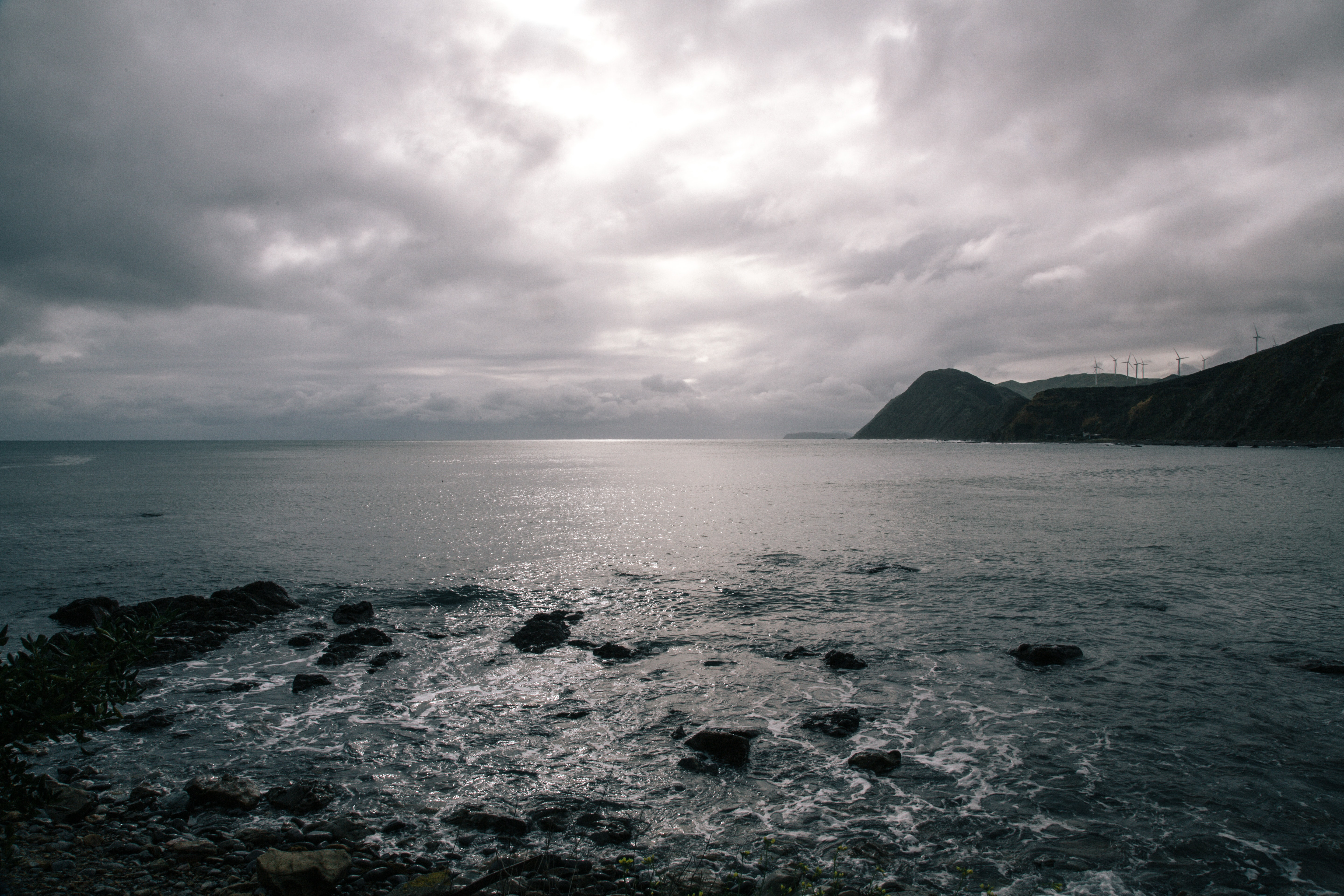 View of the ocean horizon with windmills on the coastline on a cloudy day at Makara Beach