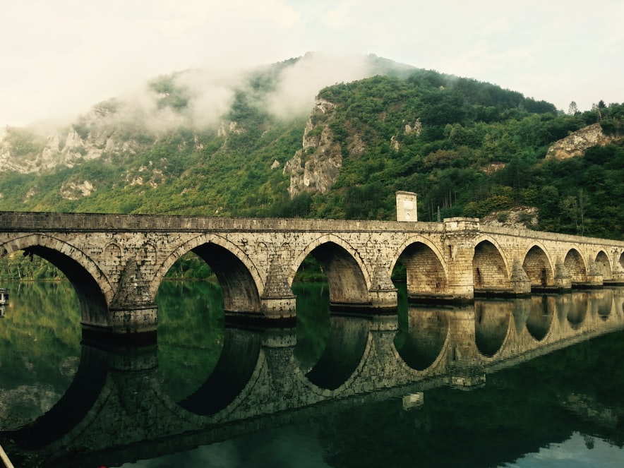 The Mehmed Paša Sokolović Bridge is a stone bridge in Višegrad, Bosnia and Herzegovina, and was completed in 1577. Photo by Torsten Muller, found at https://unsplash.com/photos/tfoqHmi-MOg
