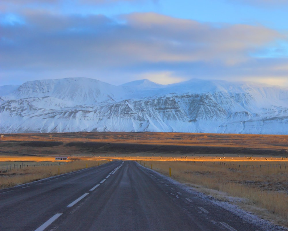 gray asphalt road in front of snow mountains