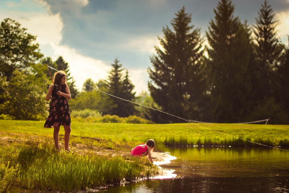 girl standing green grass field beside lake during daytime