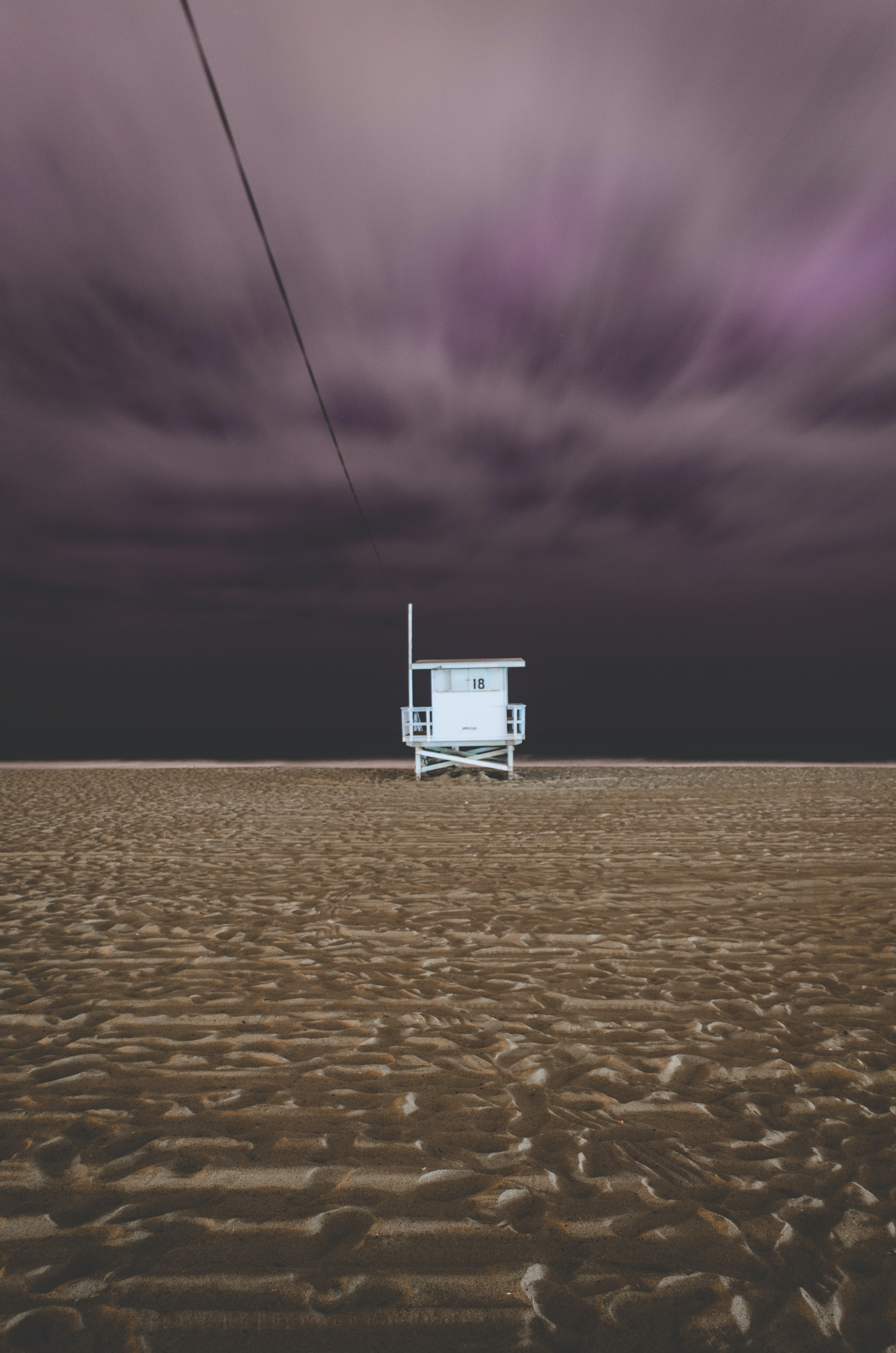 Lifeguard station on the sand beach beneath black clouds at Santa Monica