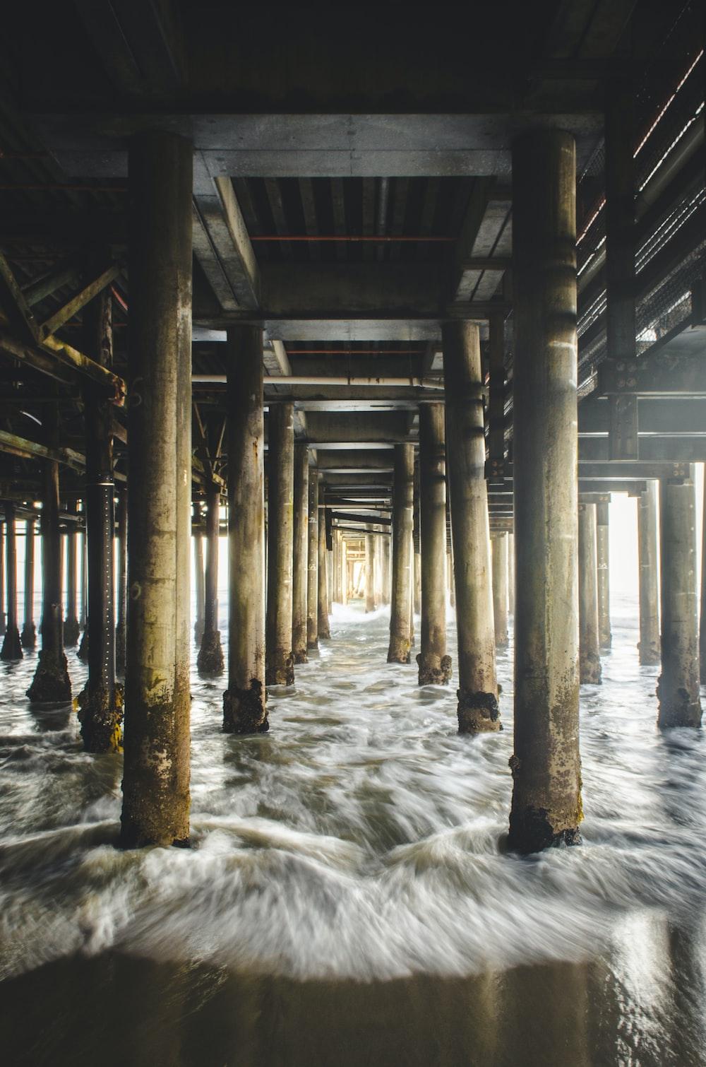brown and black wooden dock under ocean water