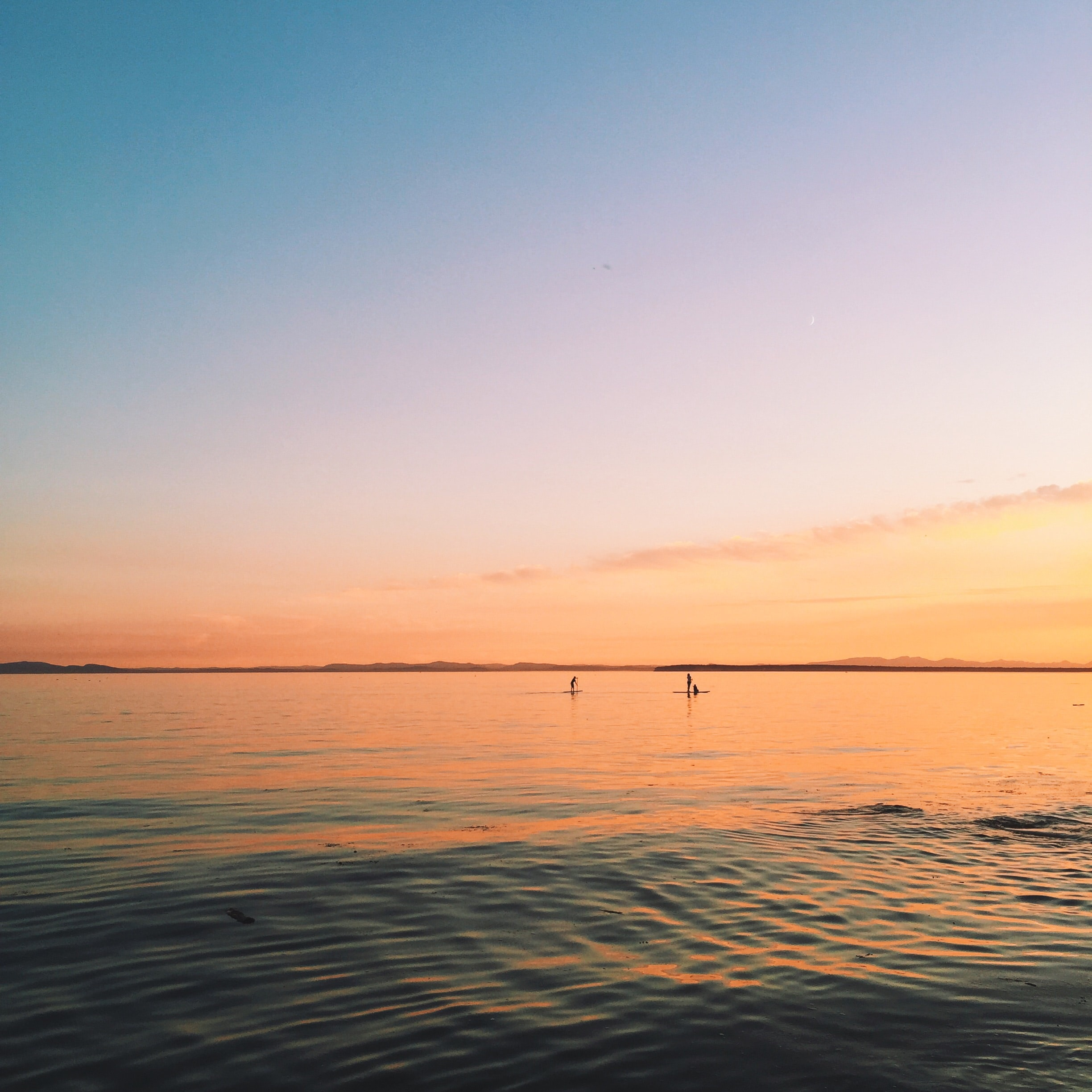 Silhouette of people rafting on calm waters during sunset